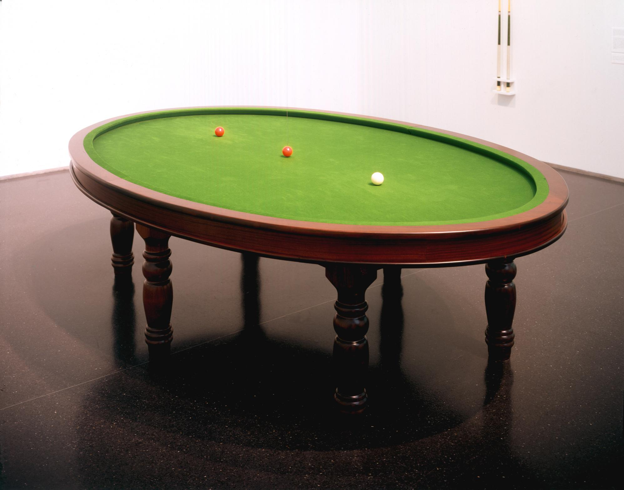 An oval pool table with three billiard balls sitting in a line on the surface