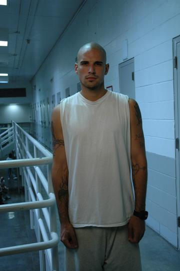 Tattooed person with mustache dressed in white tank top and grey sweatpants stands on the mezzanine of a prison looking at camera.