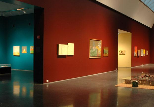 An installation view shows artworks hanging on the red-painted walls of a gallery, with another turquoise gallery to the side.