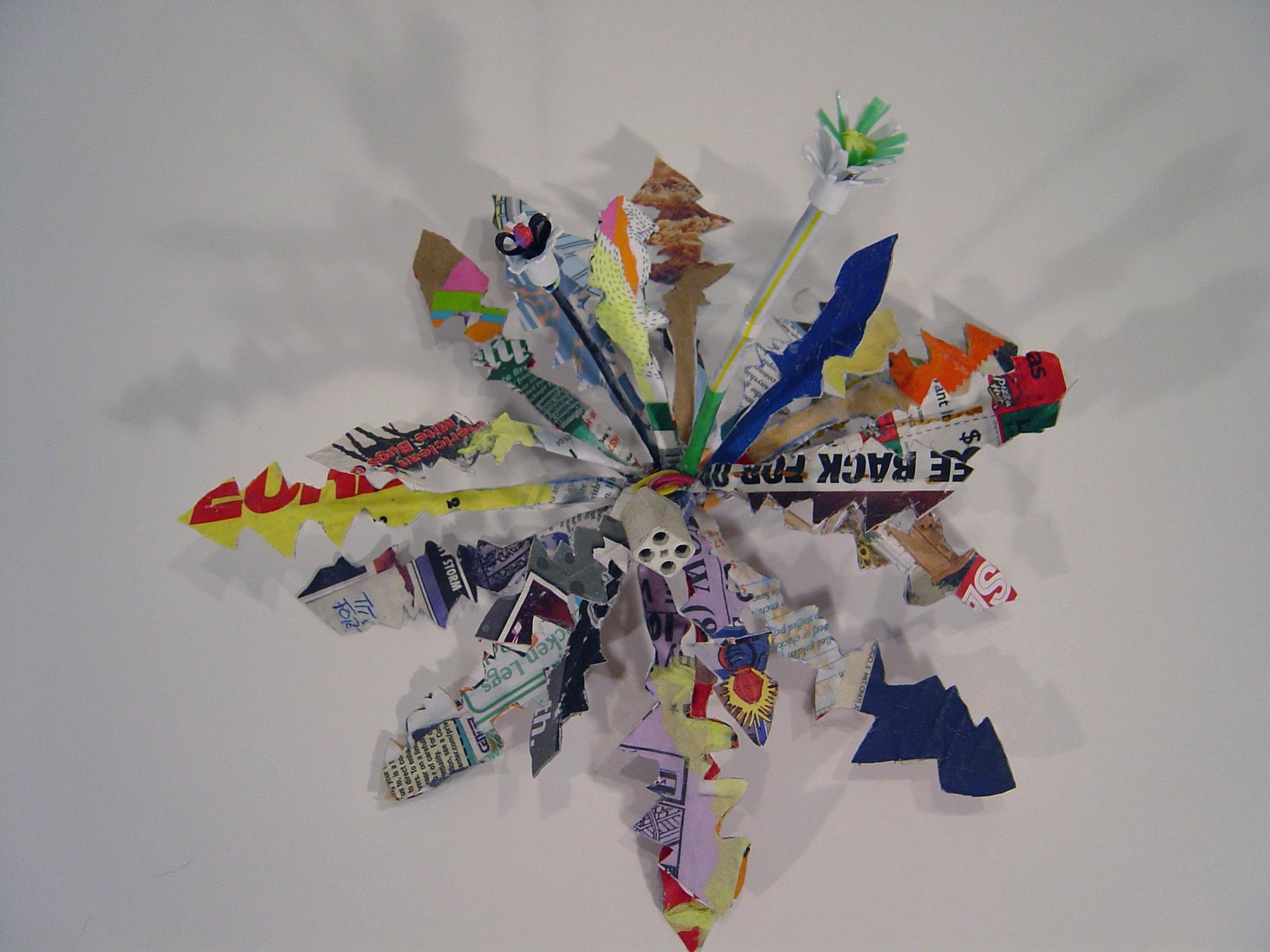 Colorful paper cut into zig-zags form a firework shaped sculpture hung on a wall