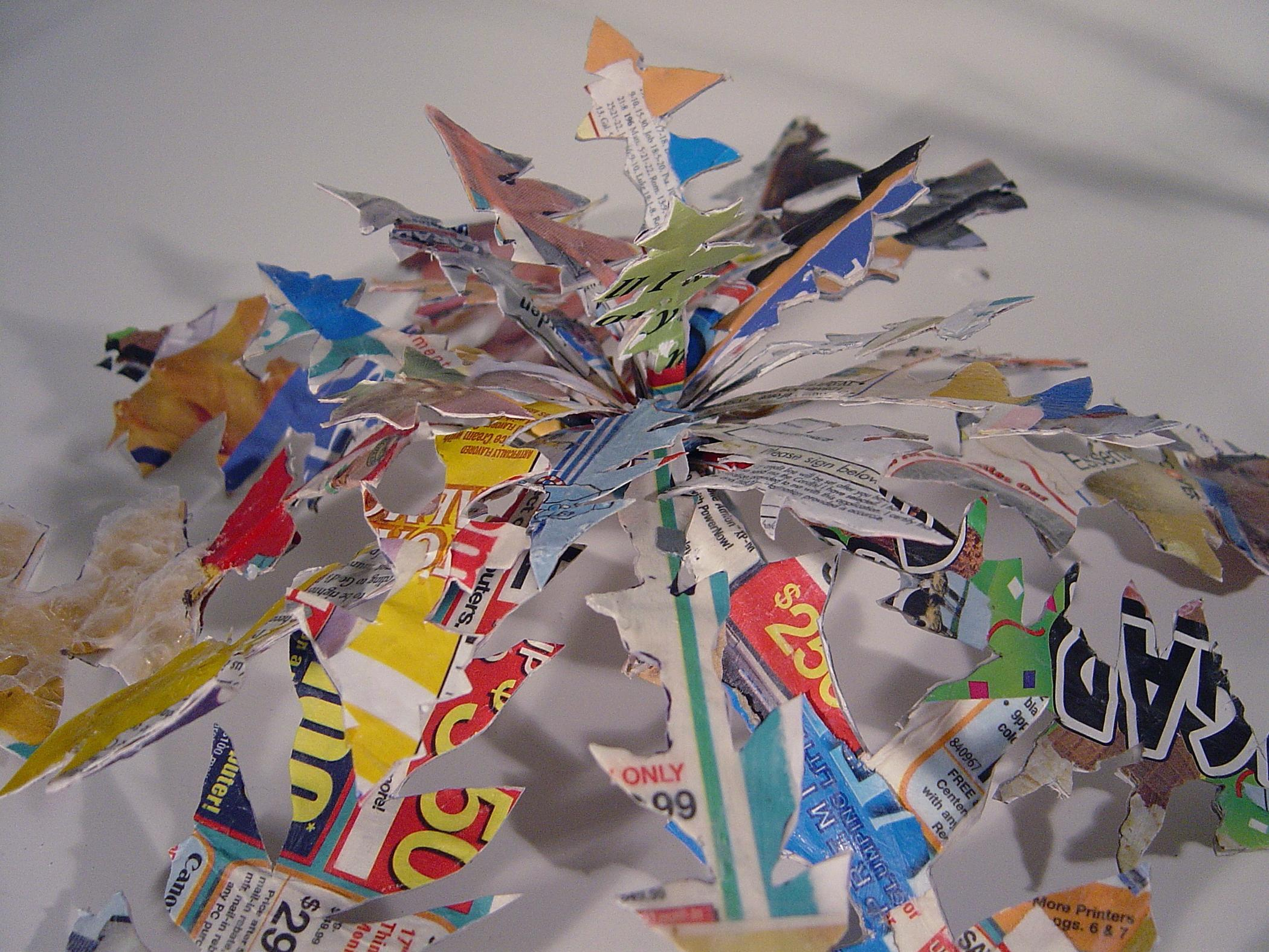 A sculpture in the shape of a plant is made out of various colorful newspaper ads.