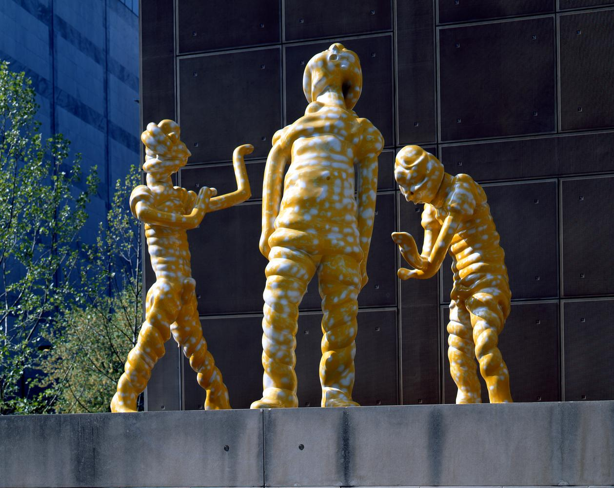 Three larger-than-life yellow figures face each other in an outdoor installation