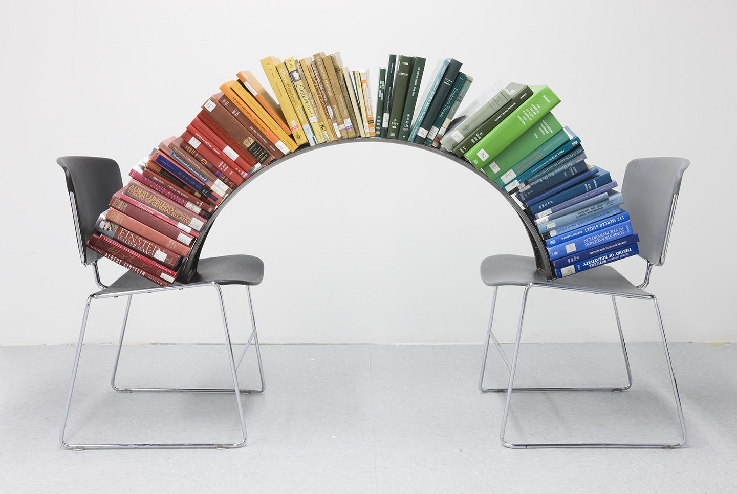A colorful, curved stack of books reaches from one chair to another.