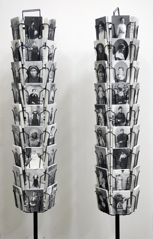 Two rotating postcard display racks hold various black-and-white portraits.