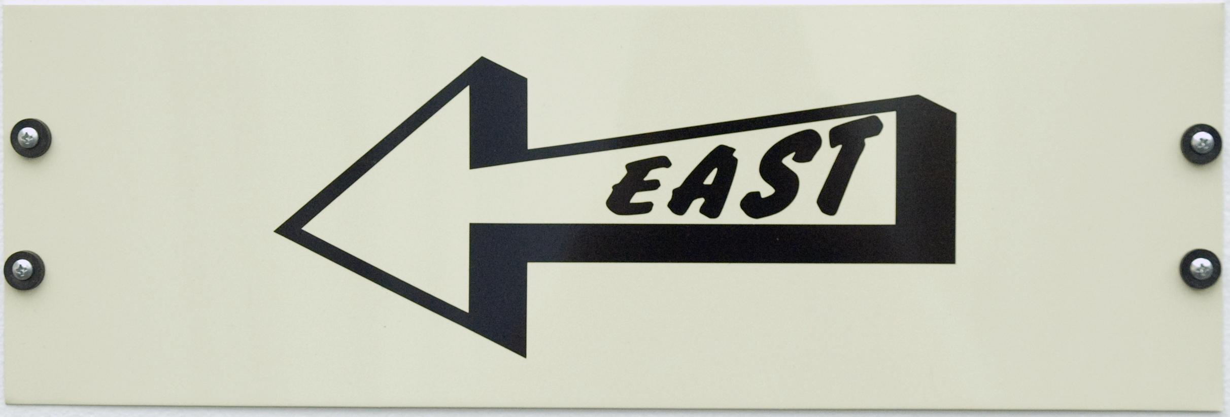 """A white sign shows a black outline of an arrow pointing to the left. Inside the arrow in black text """"EAST."""""""