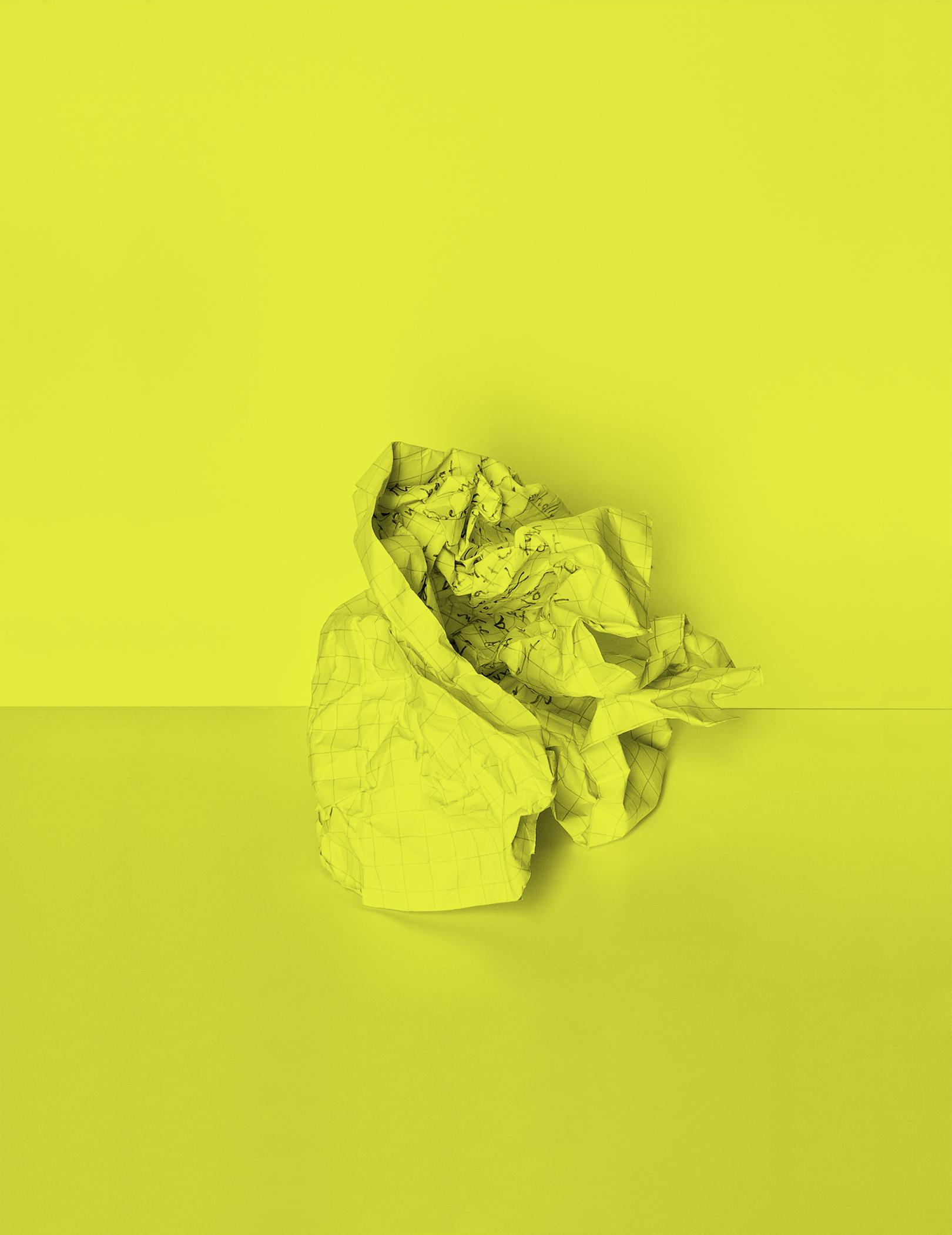 A lime green wall serves as a backdrop for a lime green ball of crumbled graph paper. The paper has words scribbled on it, which are indistinguishable due to how heavily it has been crumbled.