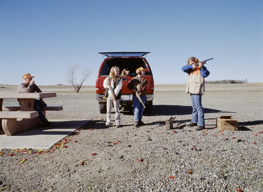 Four people are outdoors, three of whom appear to be children who are holding long-barreled guns.