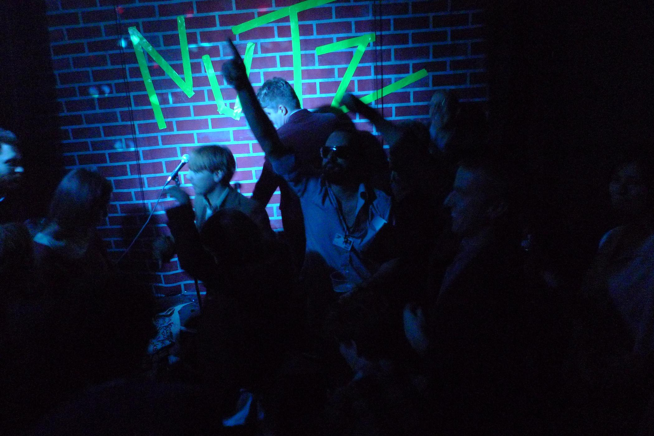 """Young people dance in dark room with a single spotlight near a brick wall with the word """"NUTZ"""" appearing in neon green tape."""