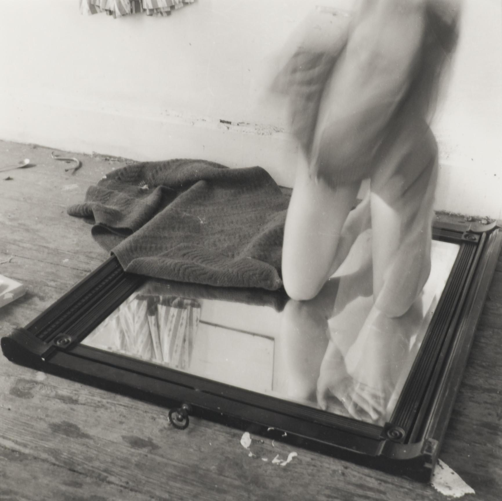 A black-and-white photograph shows a pale-skinned person kneeling on a mirror placed on the floor with a towel covering part of the mirror. The top part of the person's body is in motion and is blurry.