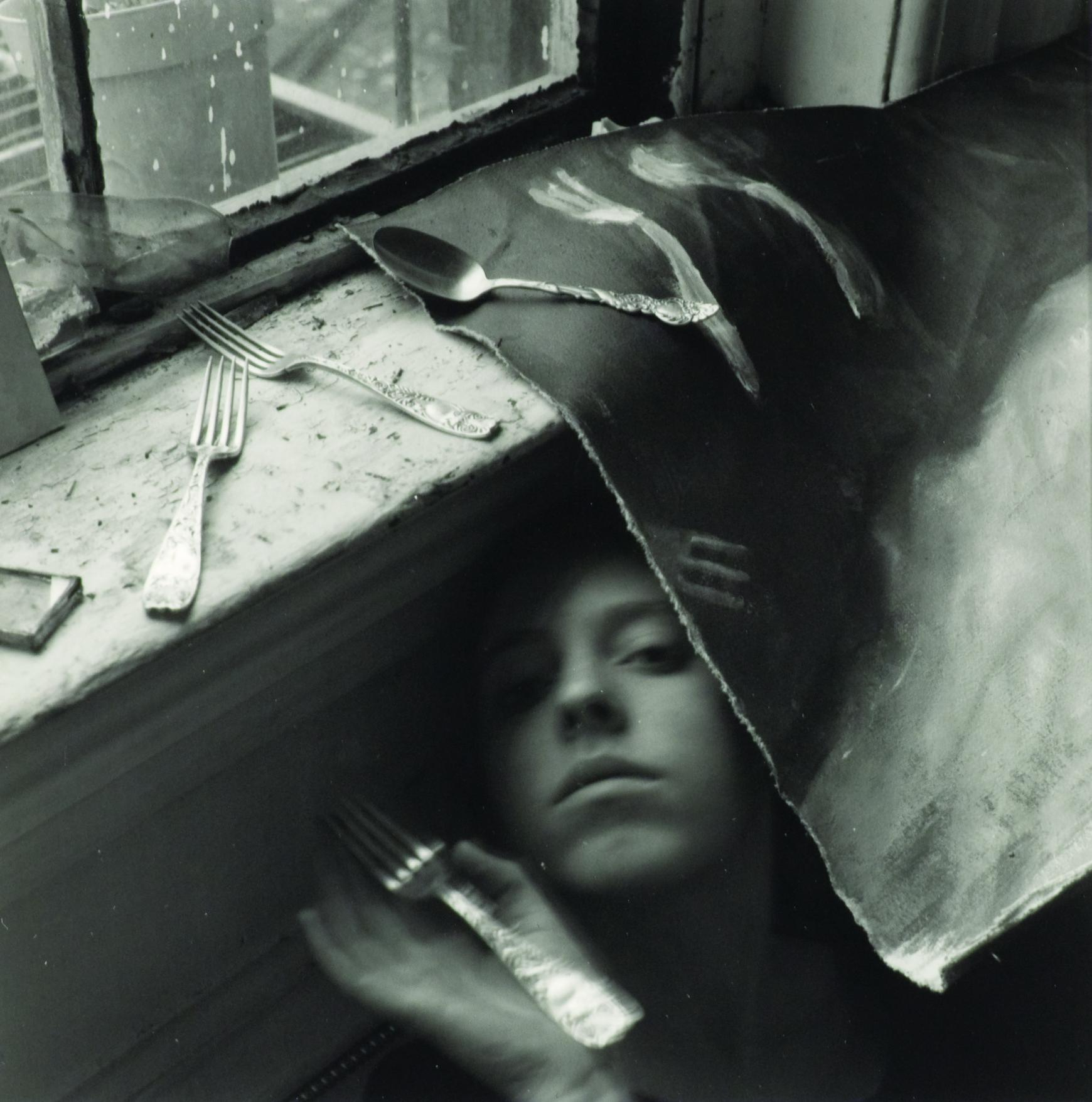 An obstructed face peers at the viewer from under a canvas sheet with forks strewn about.