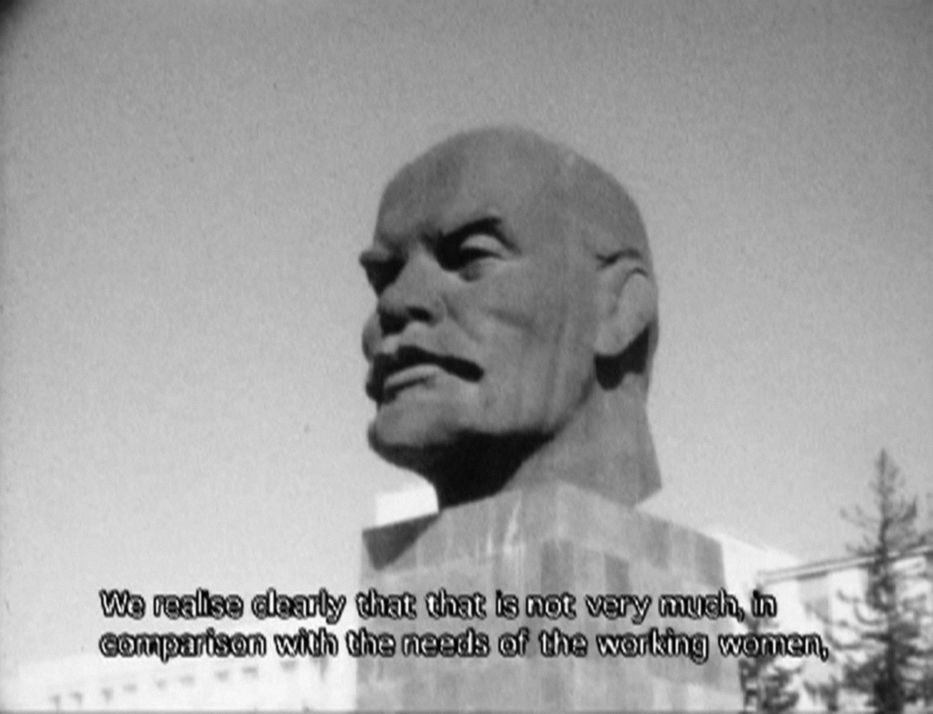 """A black-and-white image still shows a large stone bust of Vladimir Lenin's head with closed caption text reading """"We realise clearly that that is not very much, in comparison with the needs of the working women,."""""""