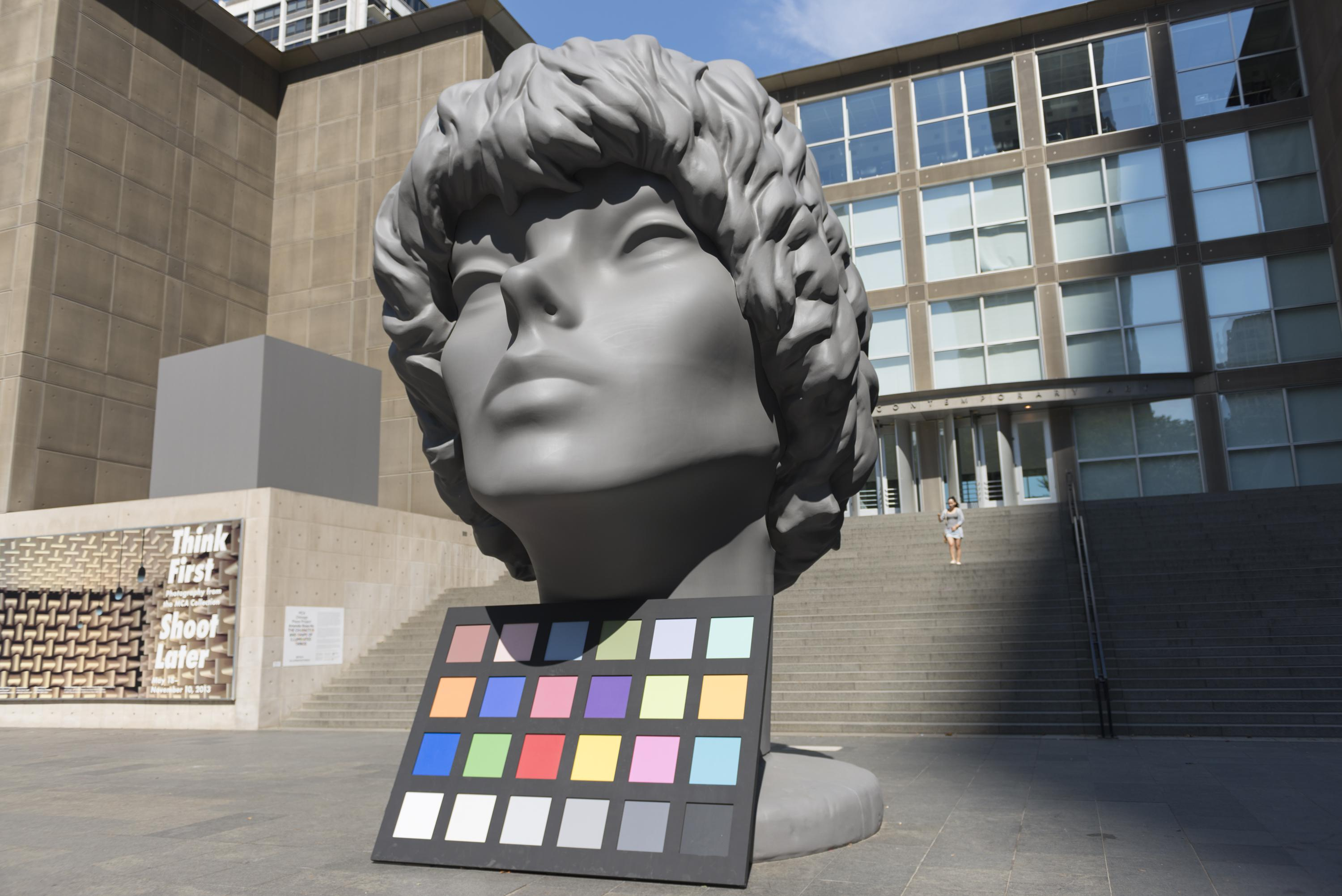 A huge sculpture of person's head is displayed along with a color palette in front of the MCA.
