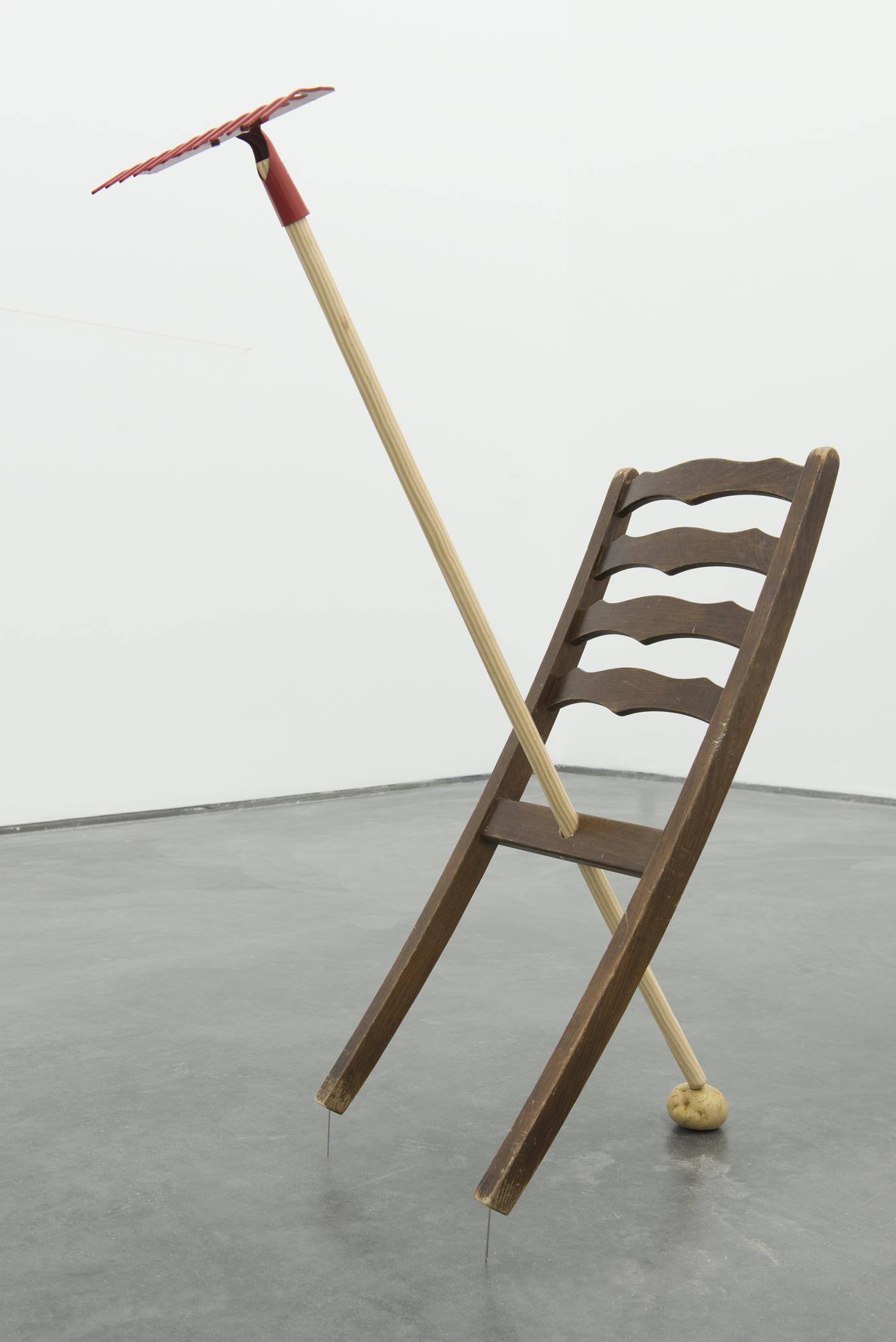 """The back portion of a slatted dinner chair has been fused with a garden hoe, forming an """"x""""."""