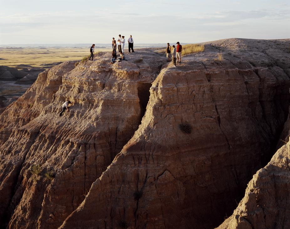 Twelve people stand on the top of a steep rock formation.