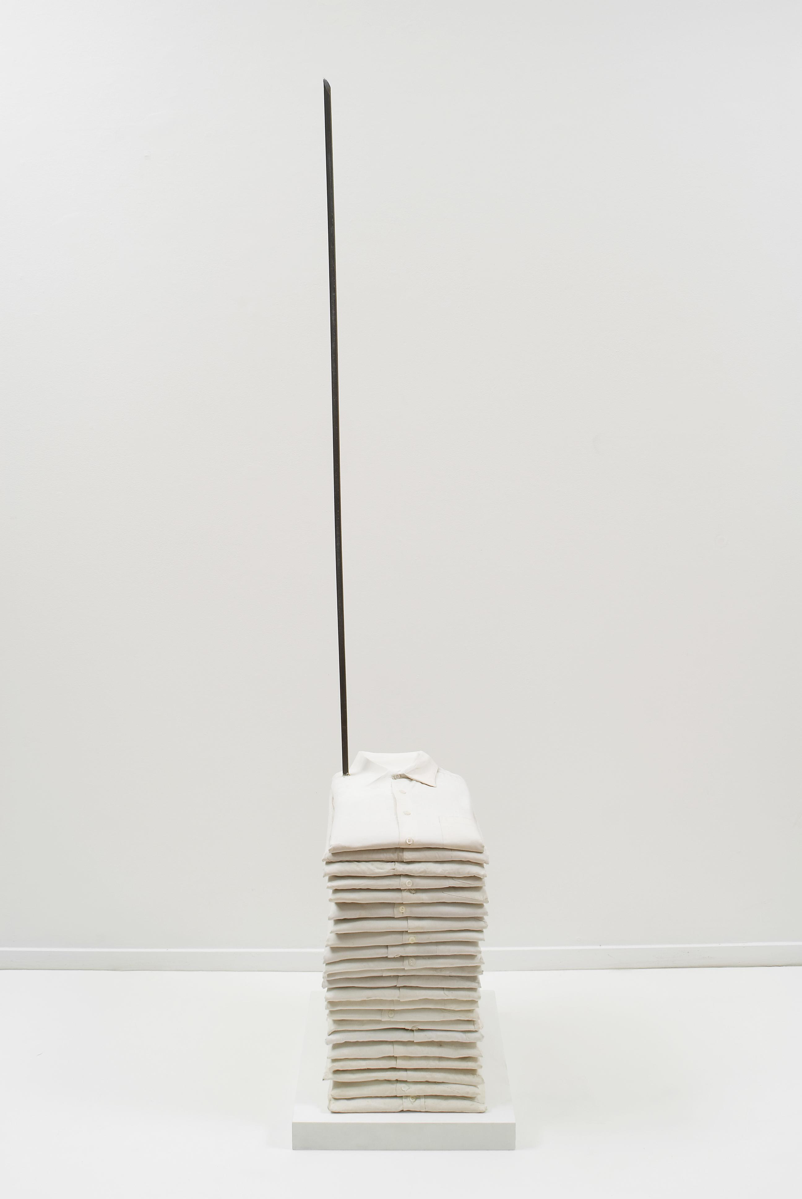 A stack of folded white polos is pierced by a vertical metal rod.