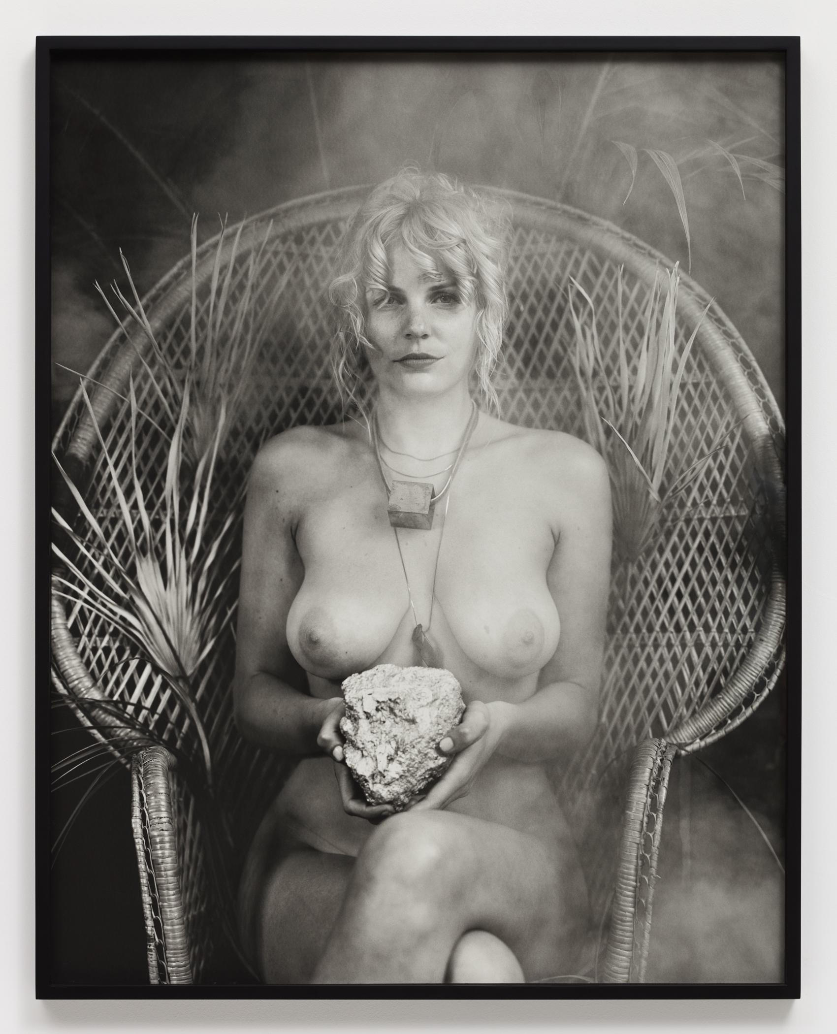 A naked, feminine person holding a rock sits in a chair.