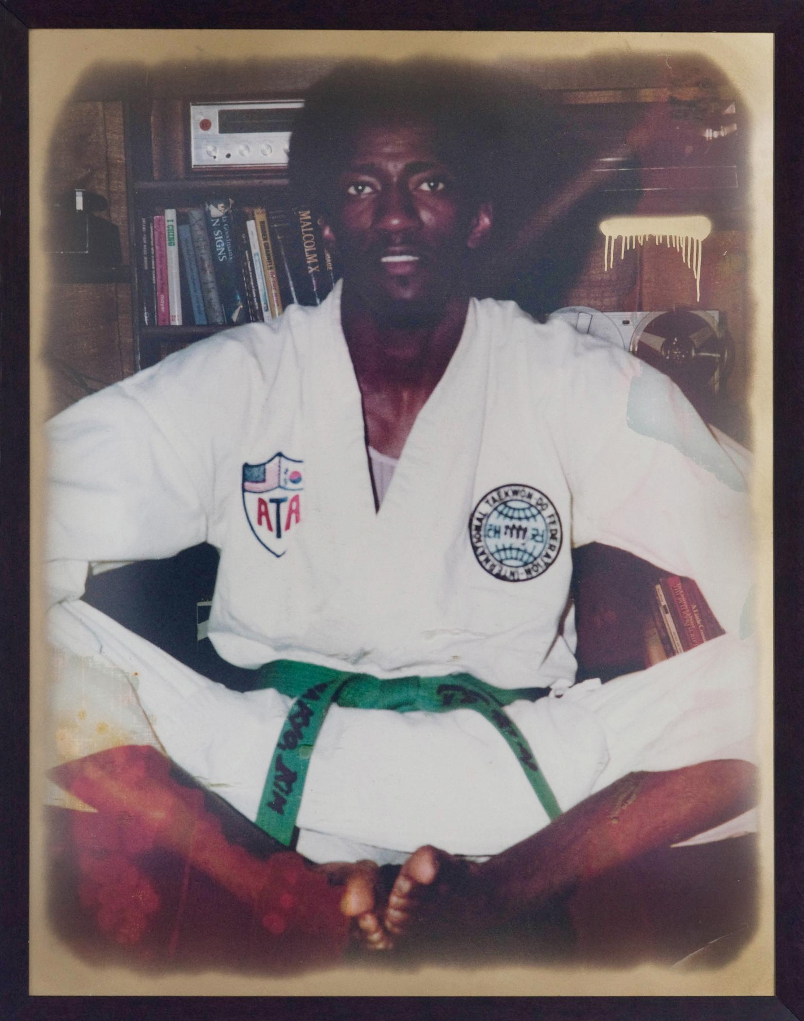 A dark-skinned person wearing a Taekwondo uniform sits on the ground.