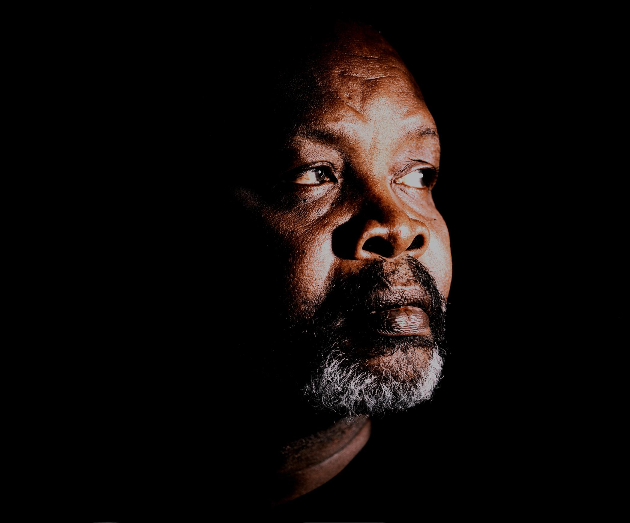 A headshot captures a dark-skinned person with a black mustache and short white beard looking off towards their left, with a black background.