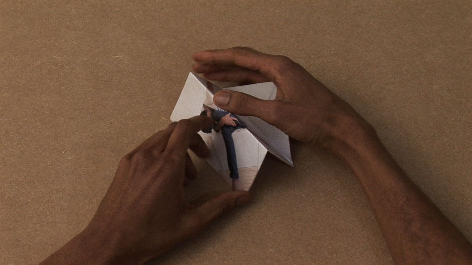 A pair of medium-dark skinned hands fold a picture of a person into a three dimensional shape