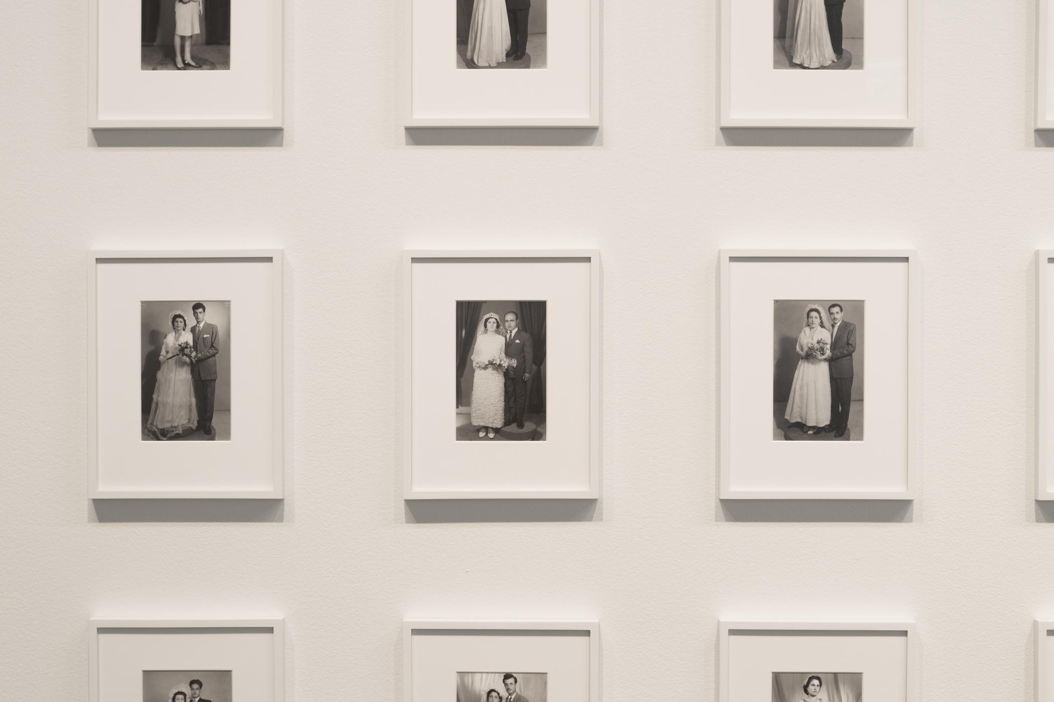 Identically sized, formal black-and-white wedding portraits are matted and framed in white, hanging in even rows on a white wall.