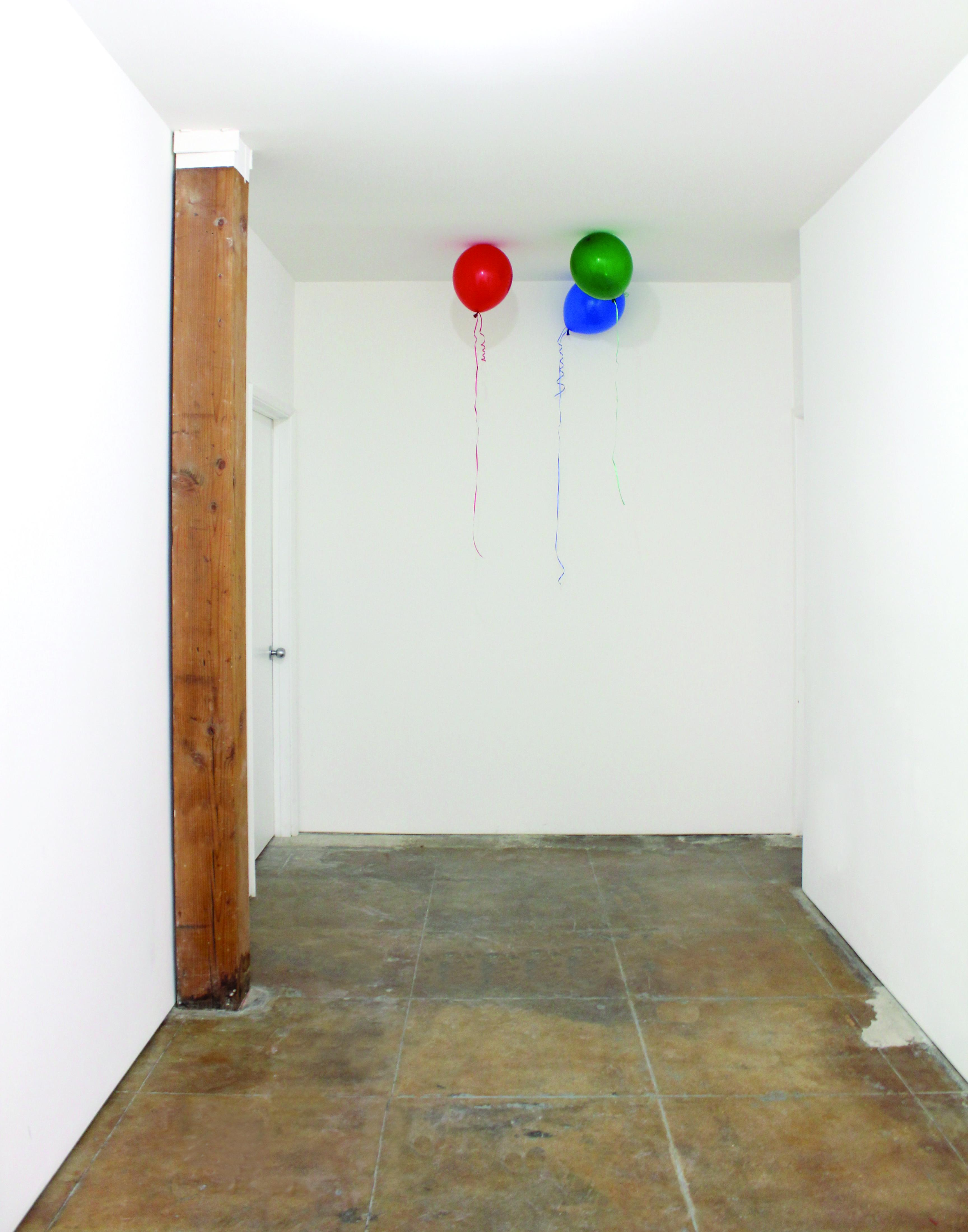 Three colorful helium balloons rest against the ceiling of a white hallway with a brown stone floor and vertical wood beam against its wall, frame left.