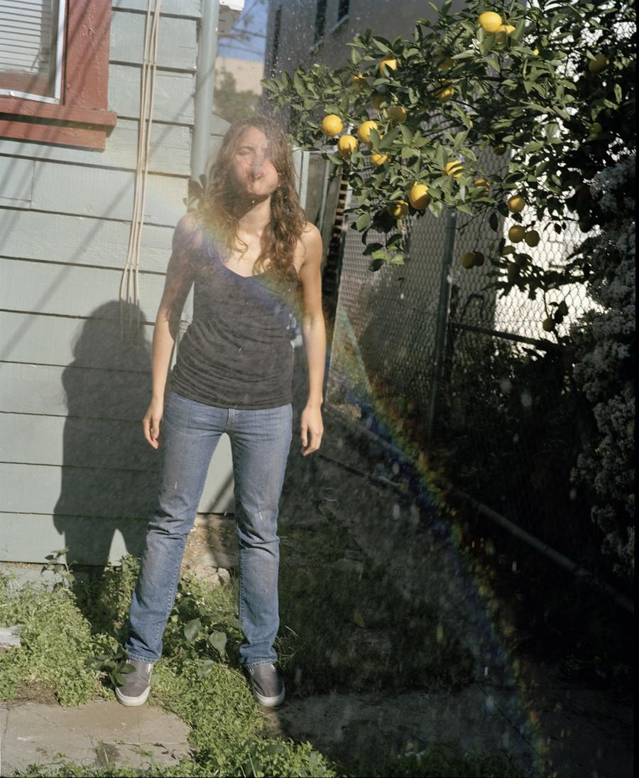 A young person is standing outdoors and spitting liquid underneath a lemon tree.