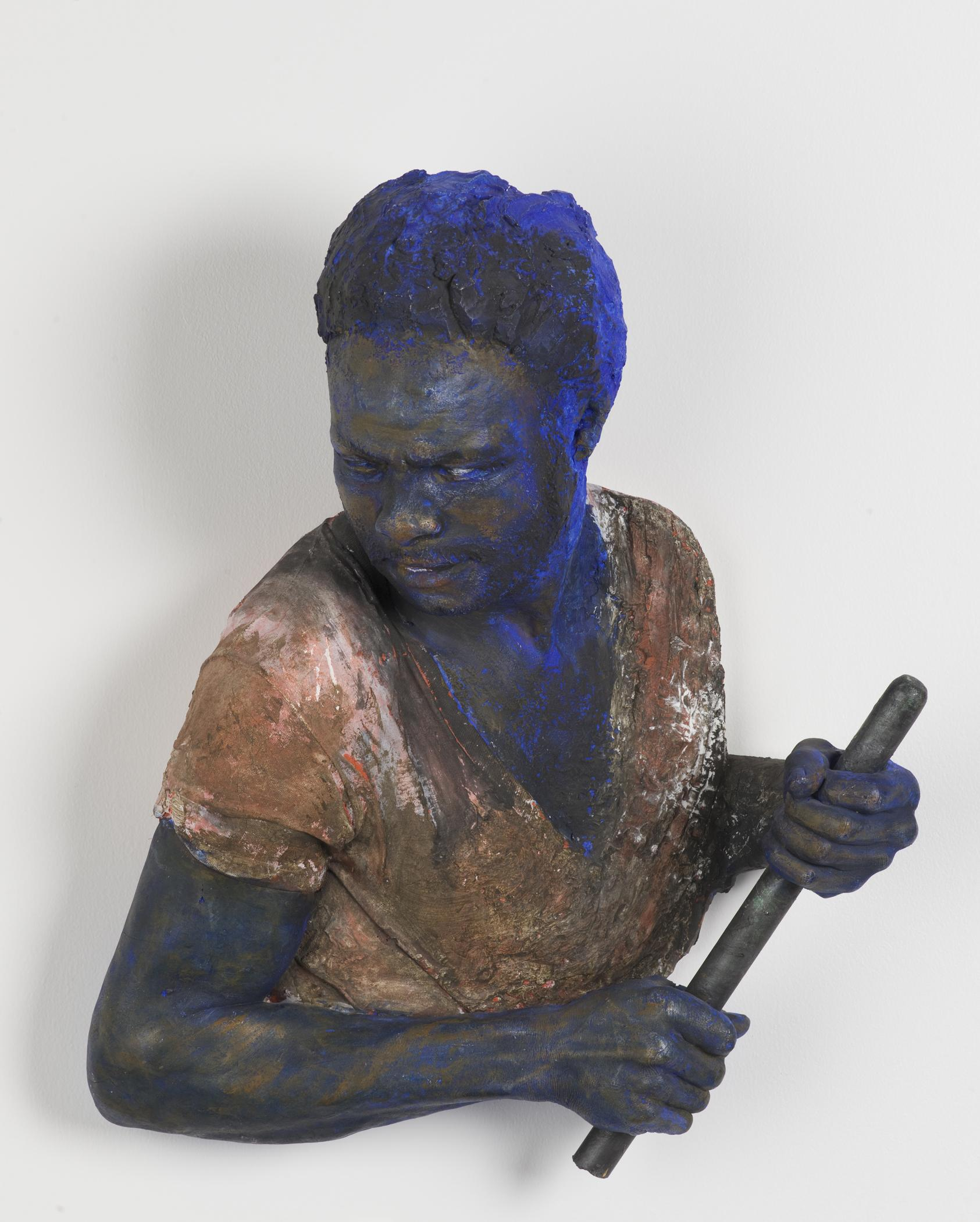 A bust of a dark-skinned person is holding a short, narrow pole while looking over their right shoulder. The bust appears to be dusted with cobalt-blue powder.