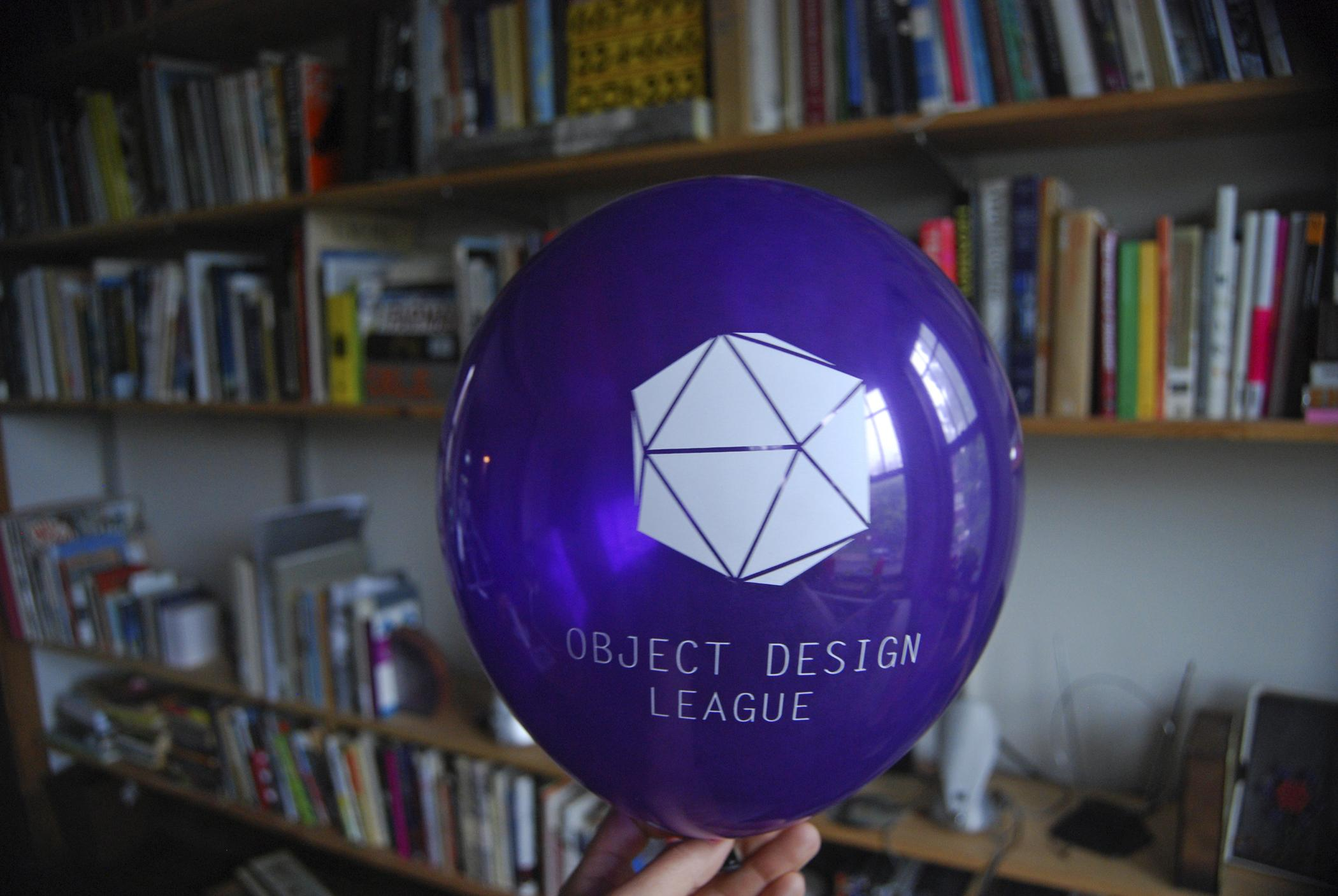 """A photograph shows a purple ballon with a geometric shape printed in white and white text """"OBJECT DESIGN LEAGUE"""" with a blurry background of several shelves of books."""