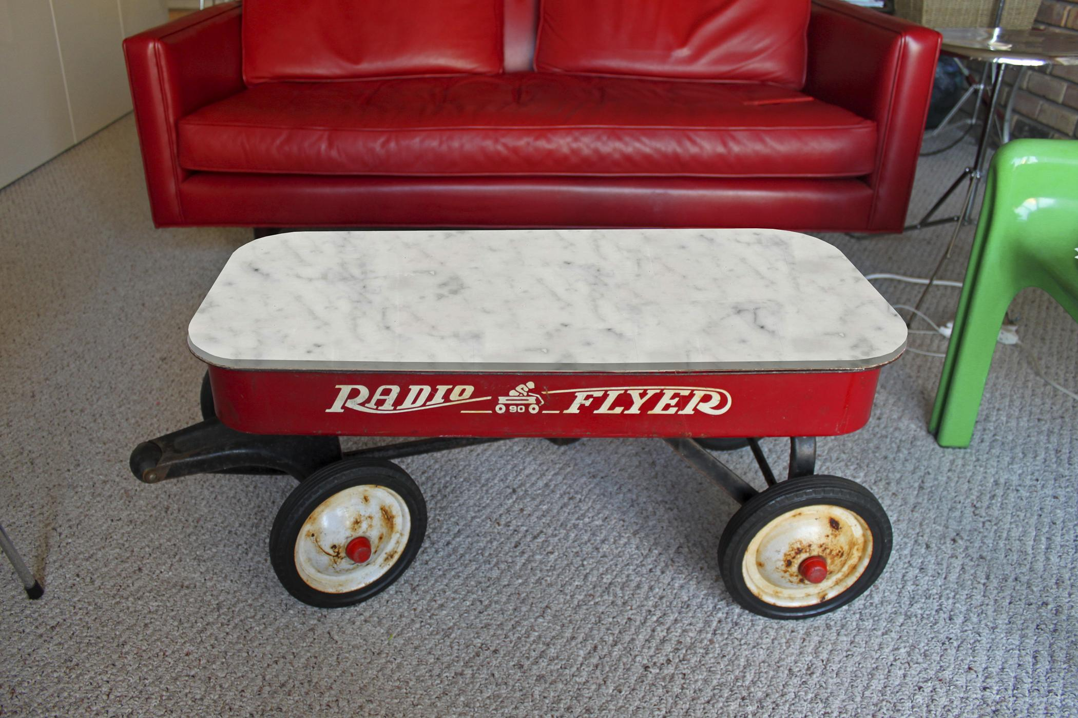 A red Radio Flyer wagon with a white marble top serves as a coffee table in a sitting room setting.
