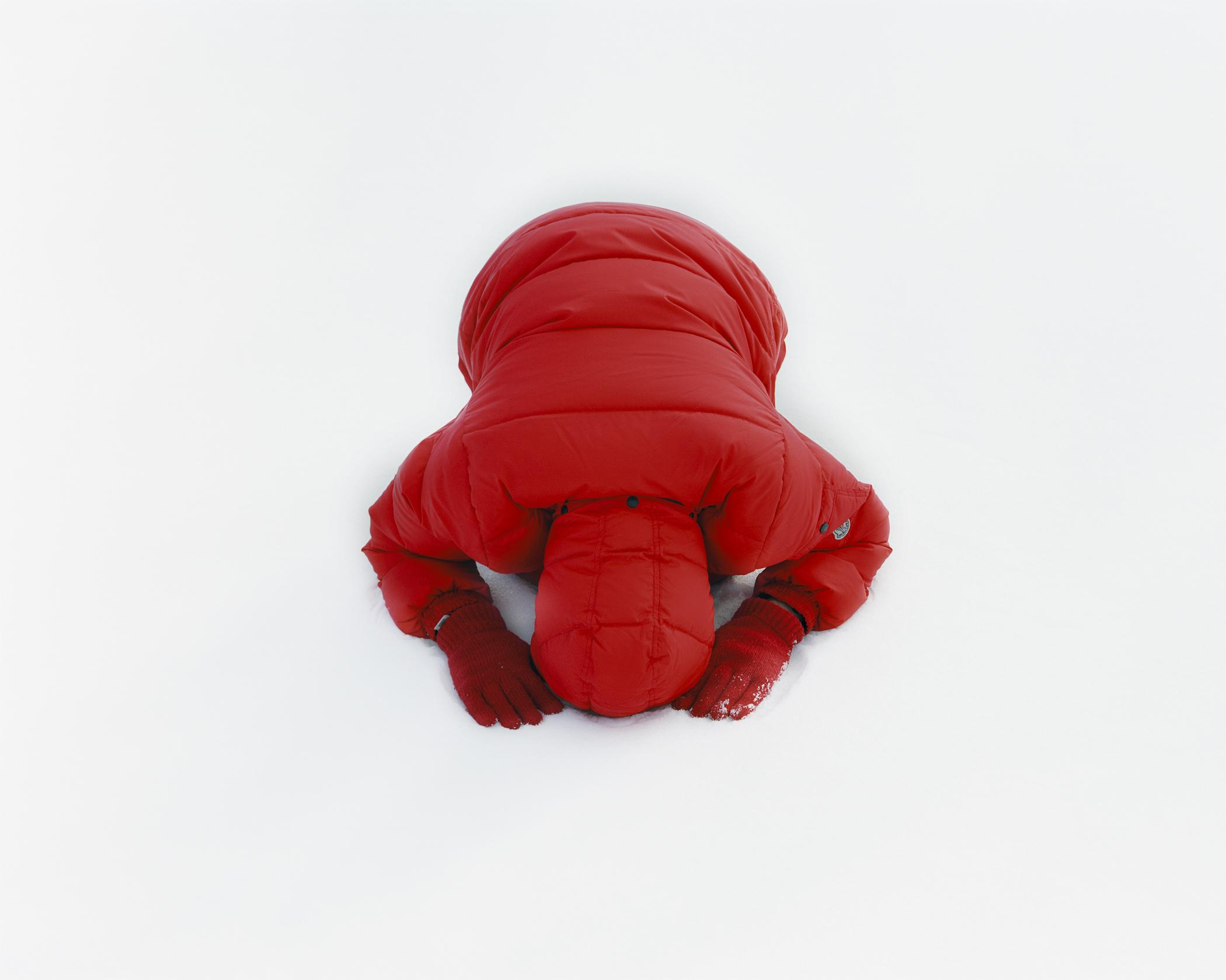A person in a red puffy coat and red gloves bows on a snow-covered surface. Their face is not seen.