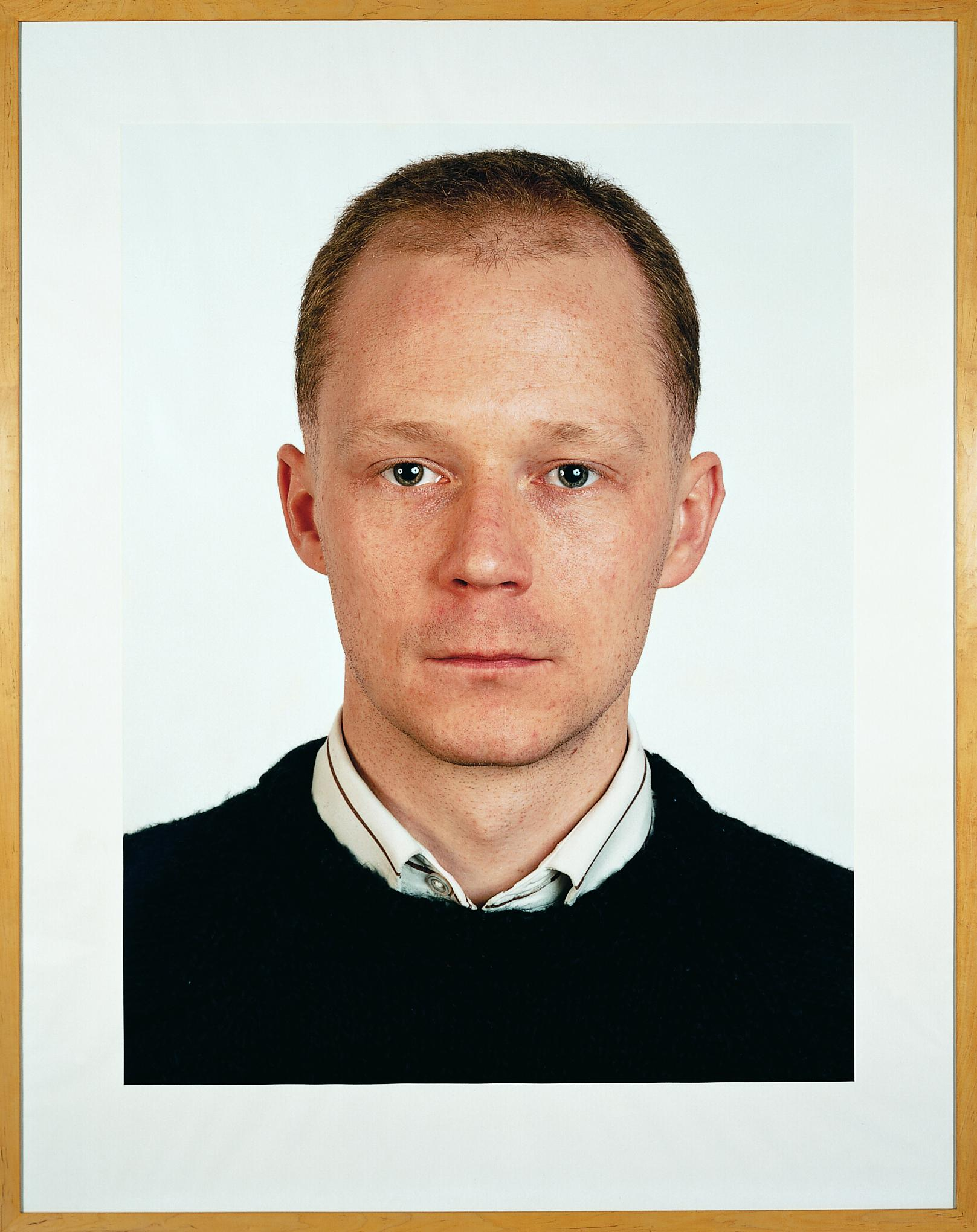 A frontal portrait features a person looking just off-camera, wearing a collared shirt under a sweater.