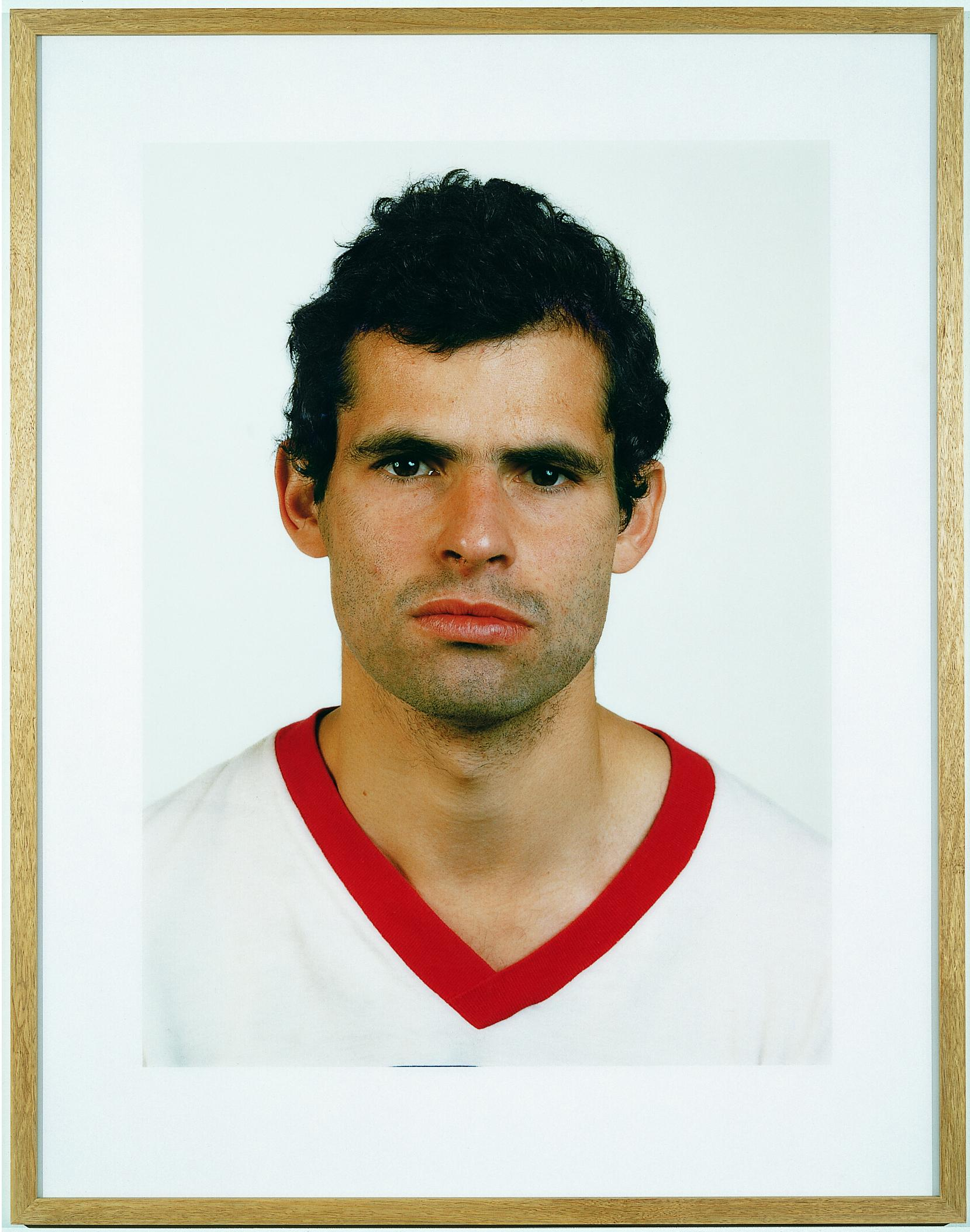 A frontal portrait features a person wearing a white shirt with a red collar.