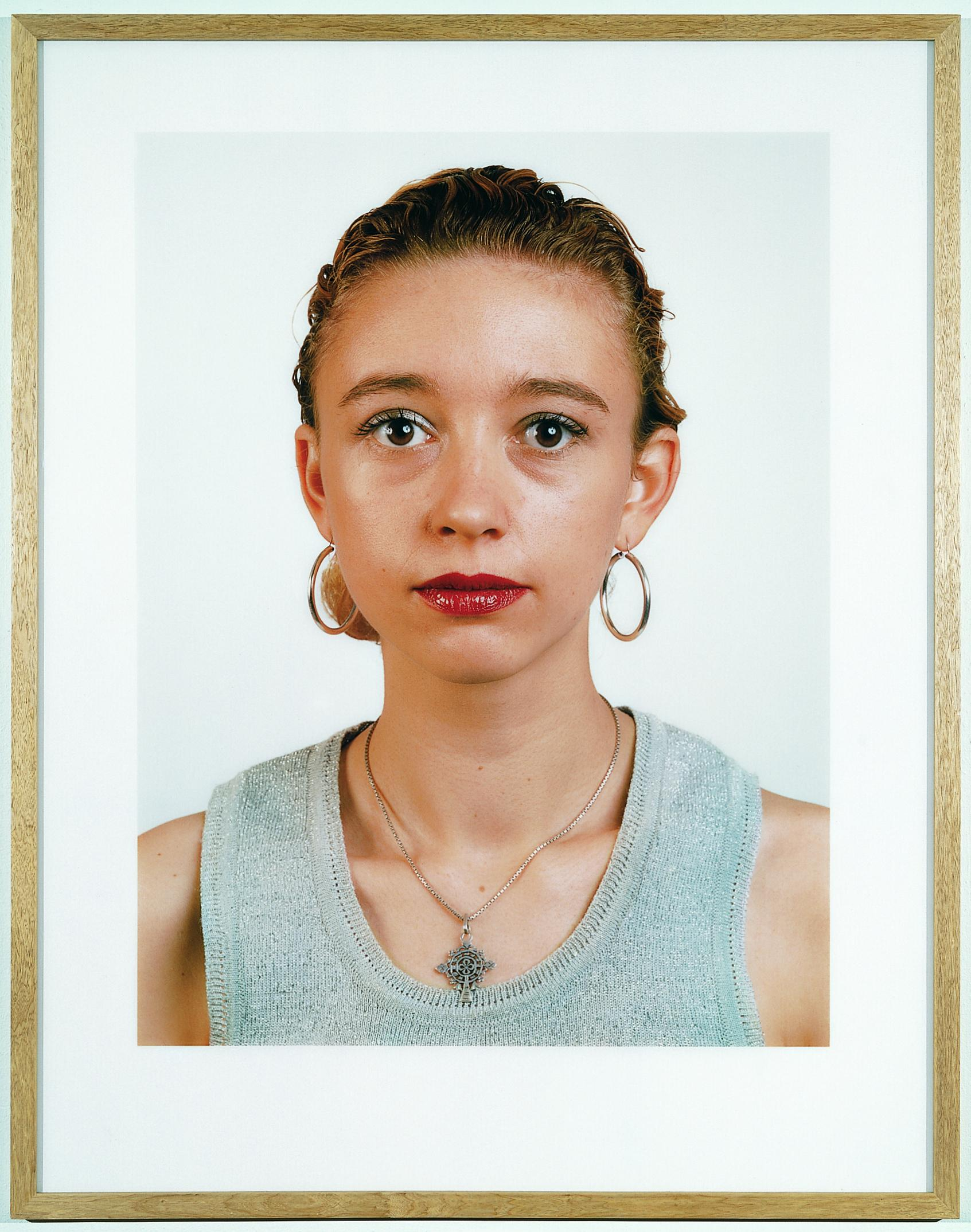 A frontal portrait features a person wearing red lipstick and a grey tank top.