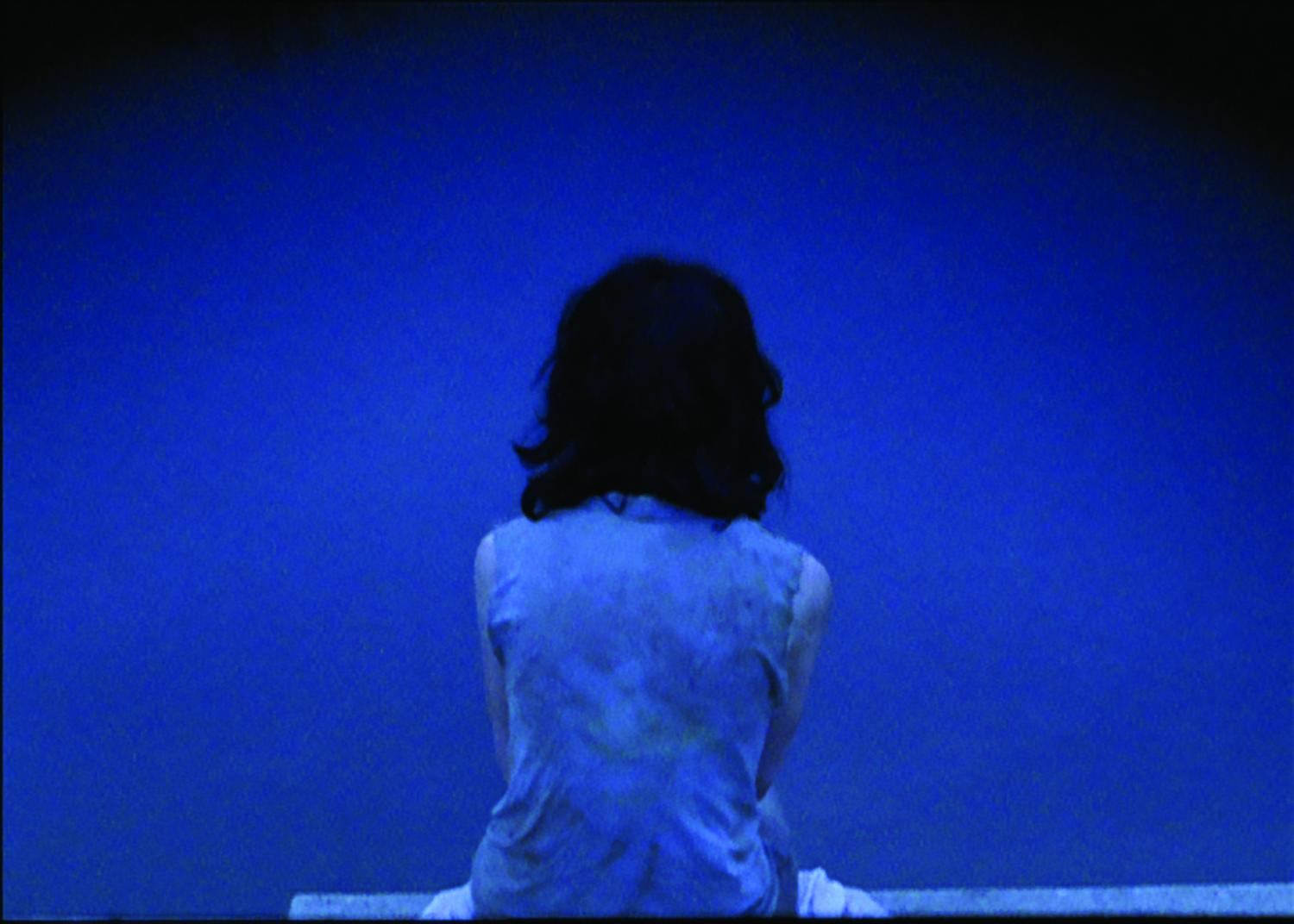 A deep blue–toned photo shows a person with shoulder-length black hair sitting with their back to the viewer.
