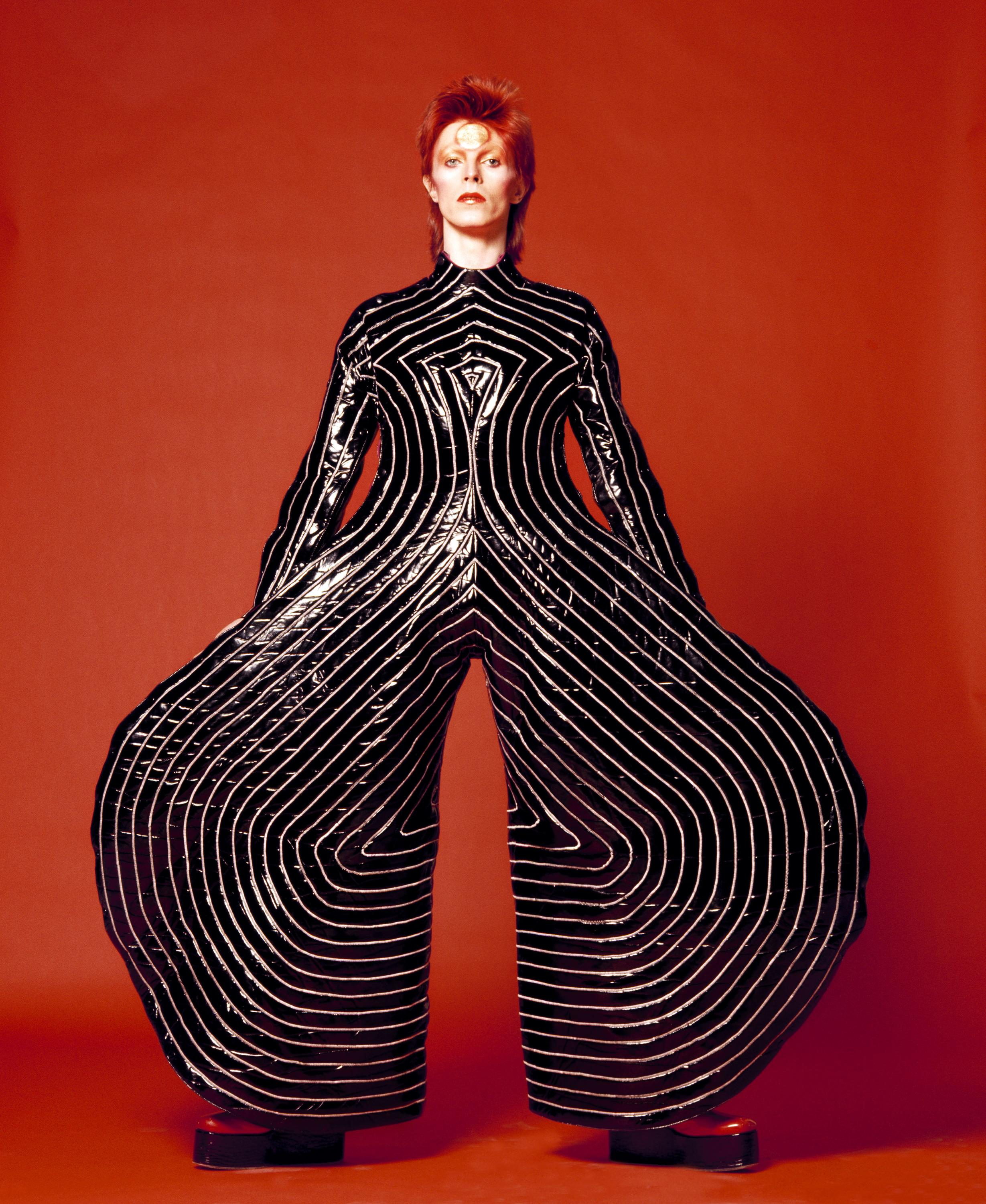 A photograph of David Bowie with pale skin and bright red hair wearing a wide-leg black jumpsuit with white stripes in front of a red background.