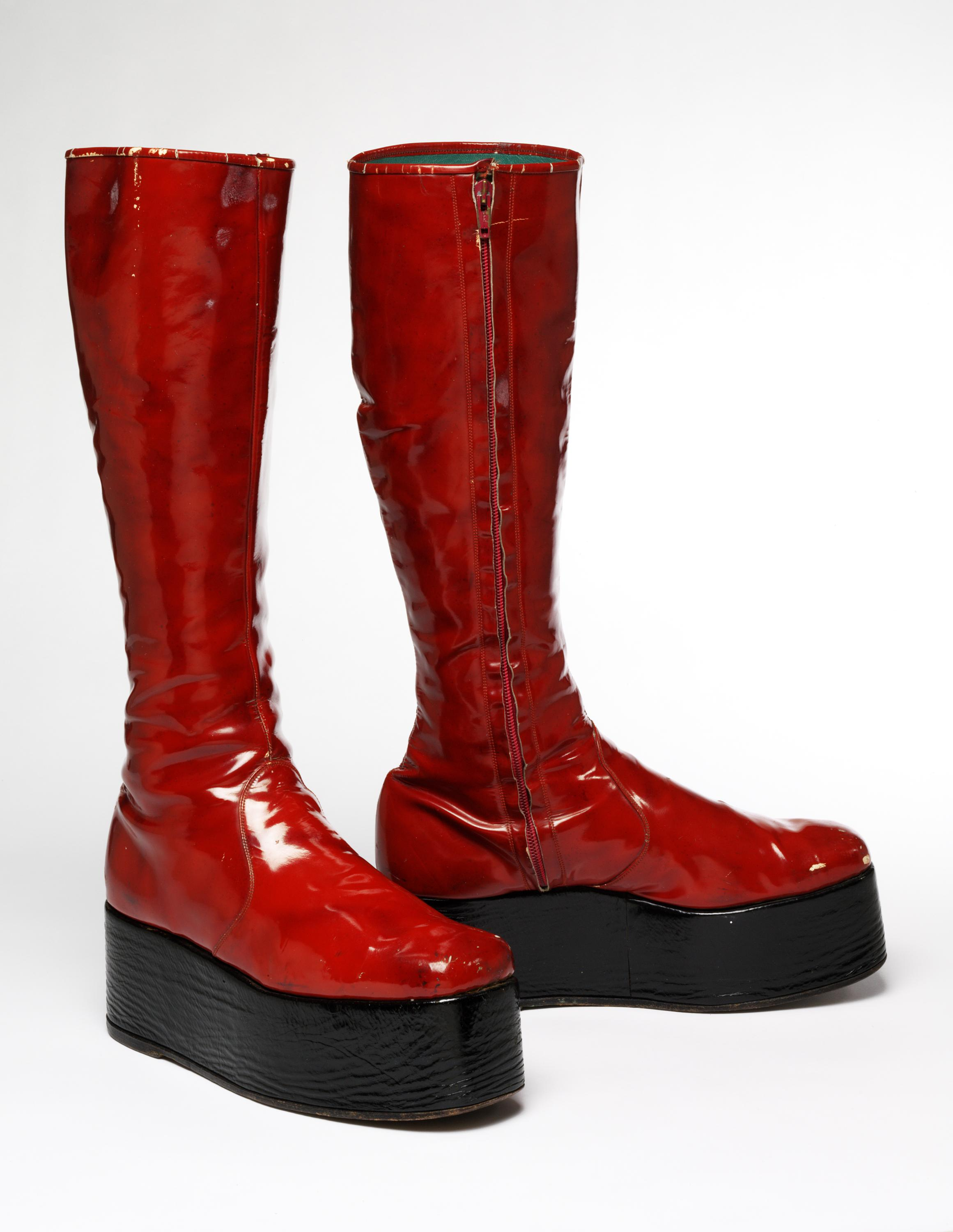 Red, chunky, high-top platform boots stand erect in a white room.