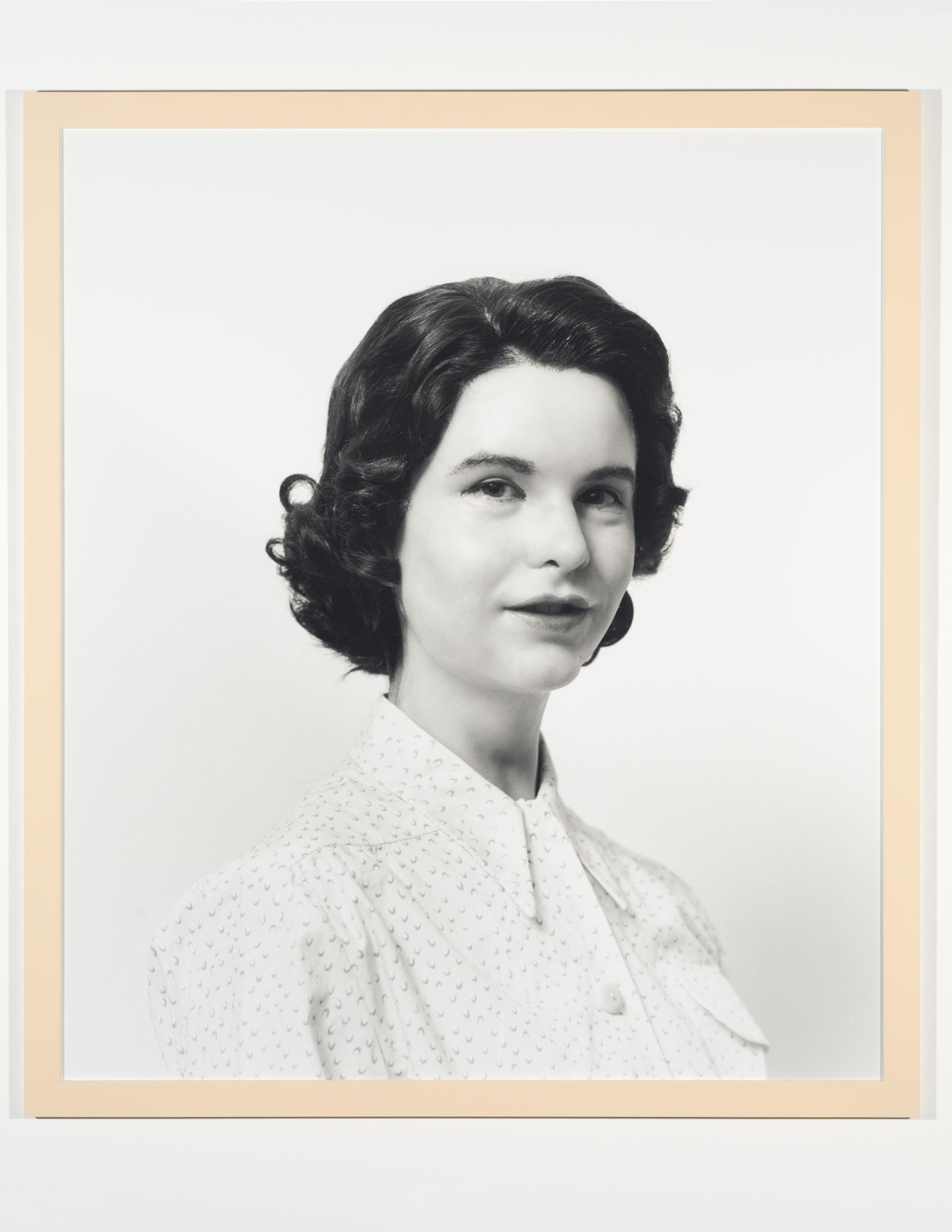 A black-and-white photograph portrait shows a pale-skinned person with short dark hair wearing a white blouse in front of a white background.