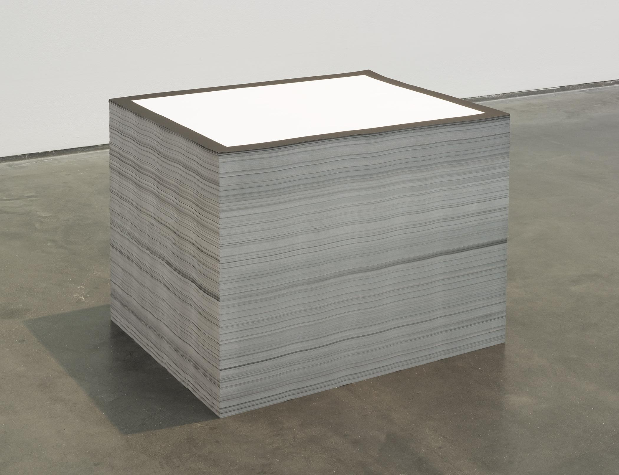 A large and neat stack of white paper with a black border sits on a concrete floor.