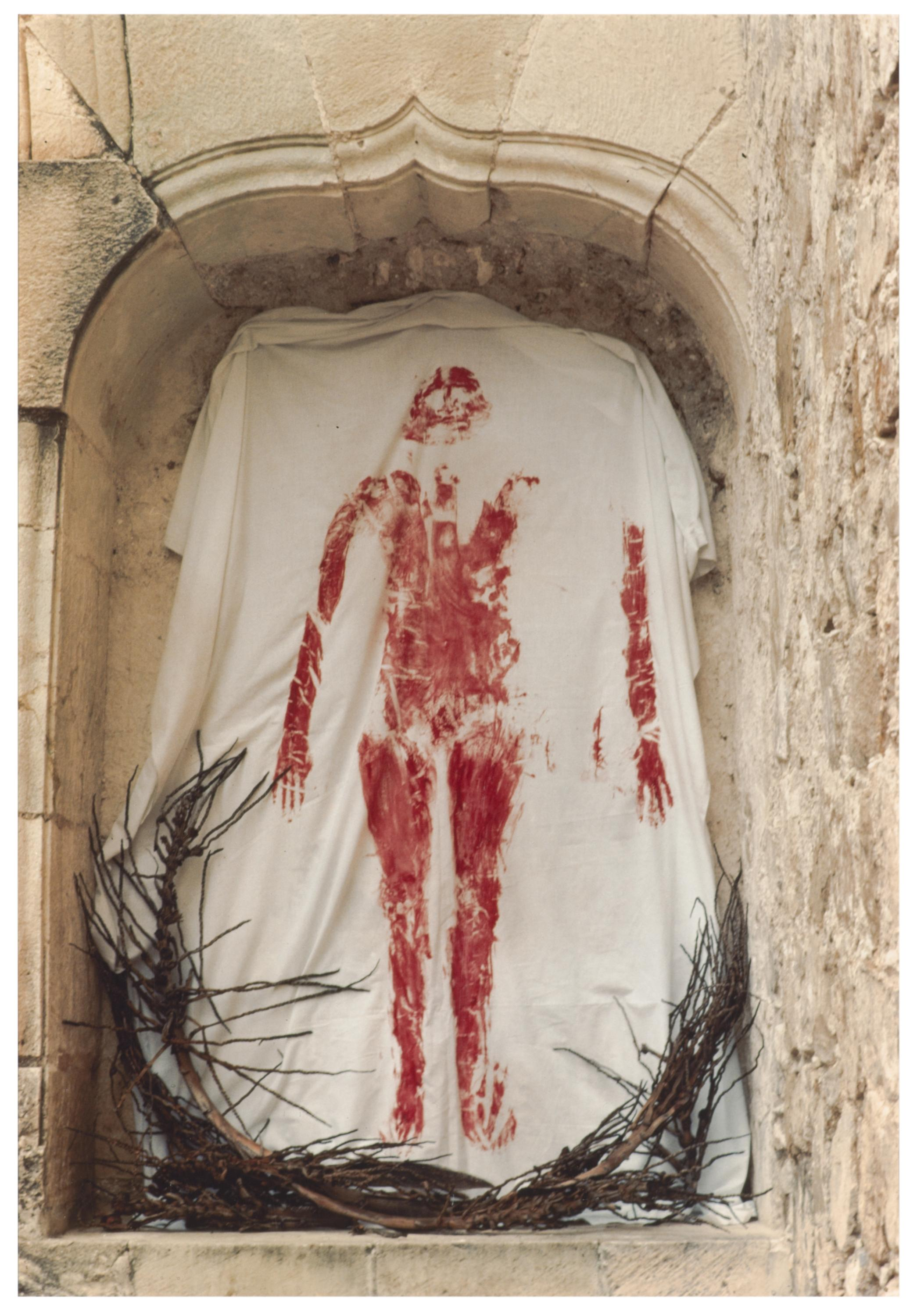 A white sheet with a blood-red imprint of a body hangs in a stone niche.