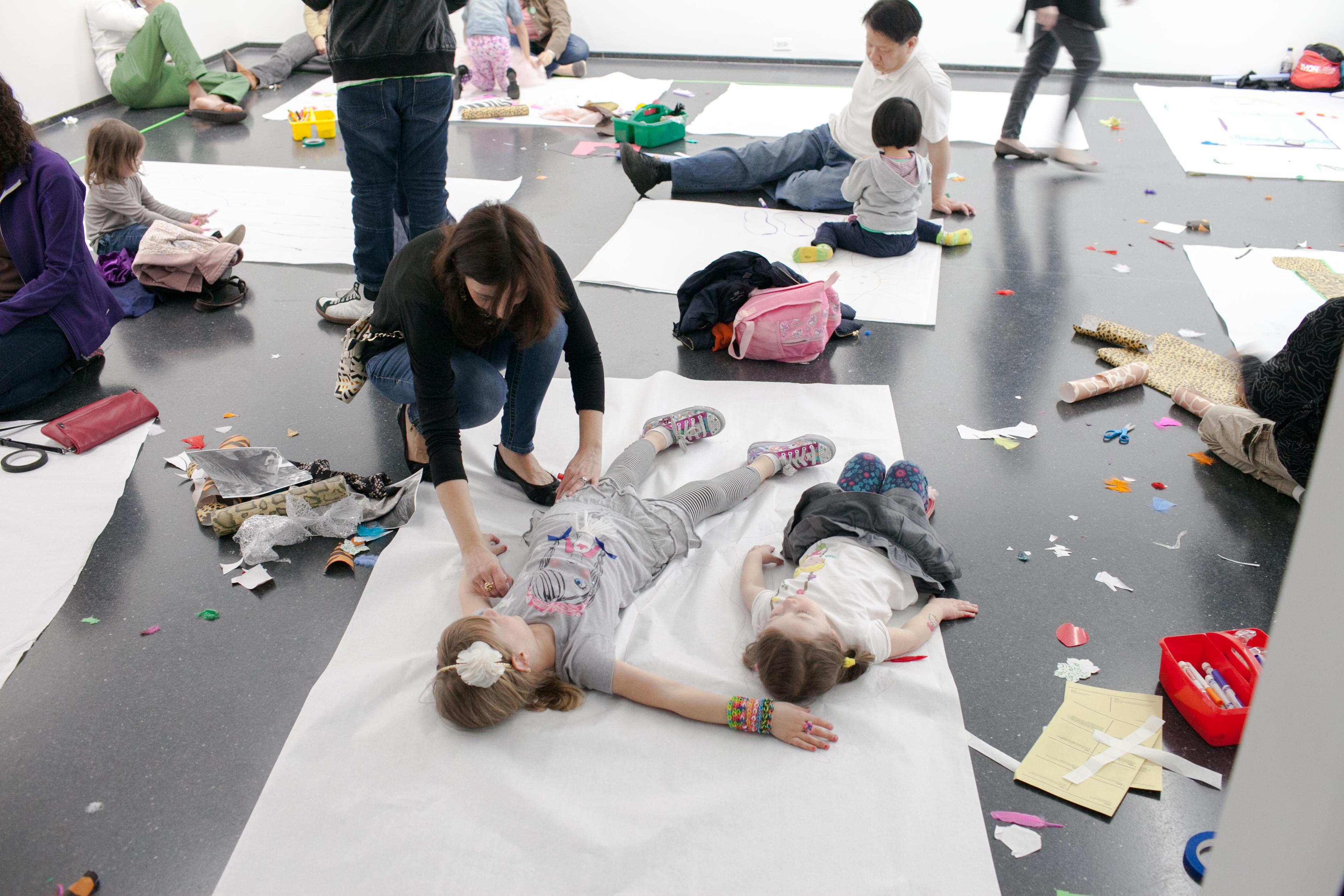 Parents and children interacting together in a white-walled gallery, with children lying down on large sheets of white craft paper while their parents trace the outline of their bodies.