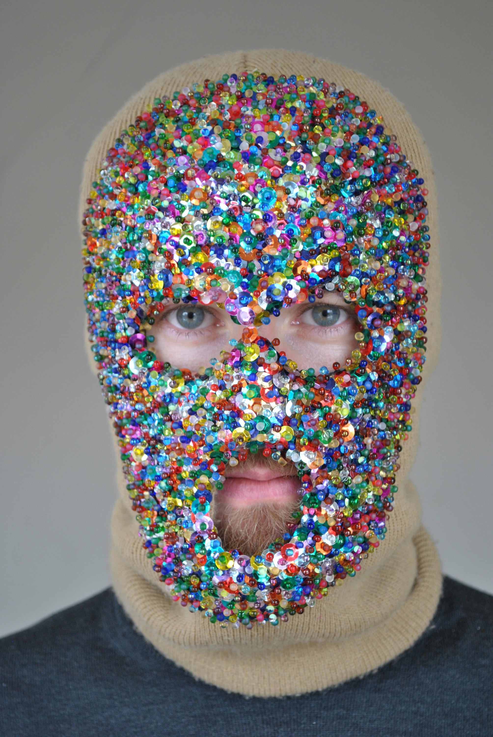 A man wearing a beige knit balaclava, the front of which is covered with multi-colored sequins