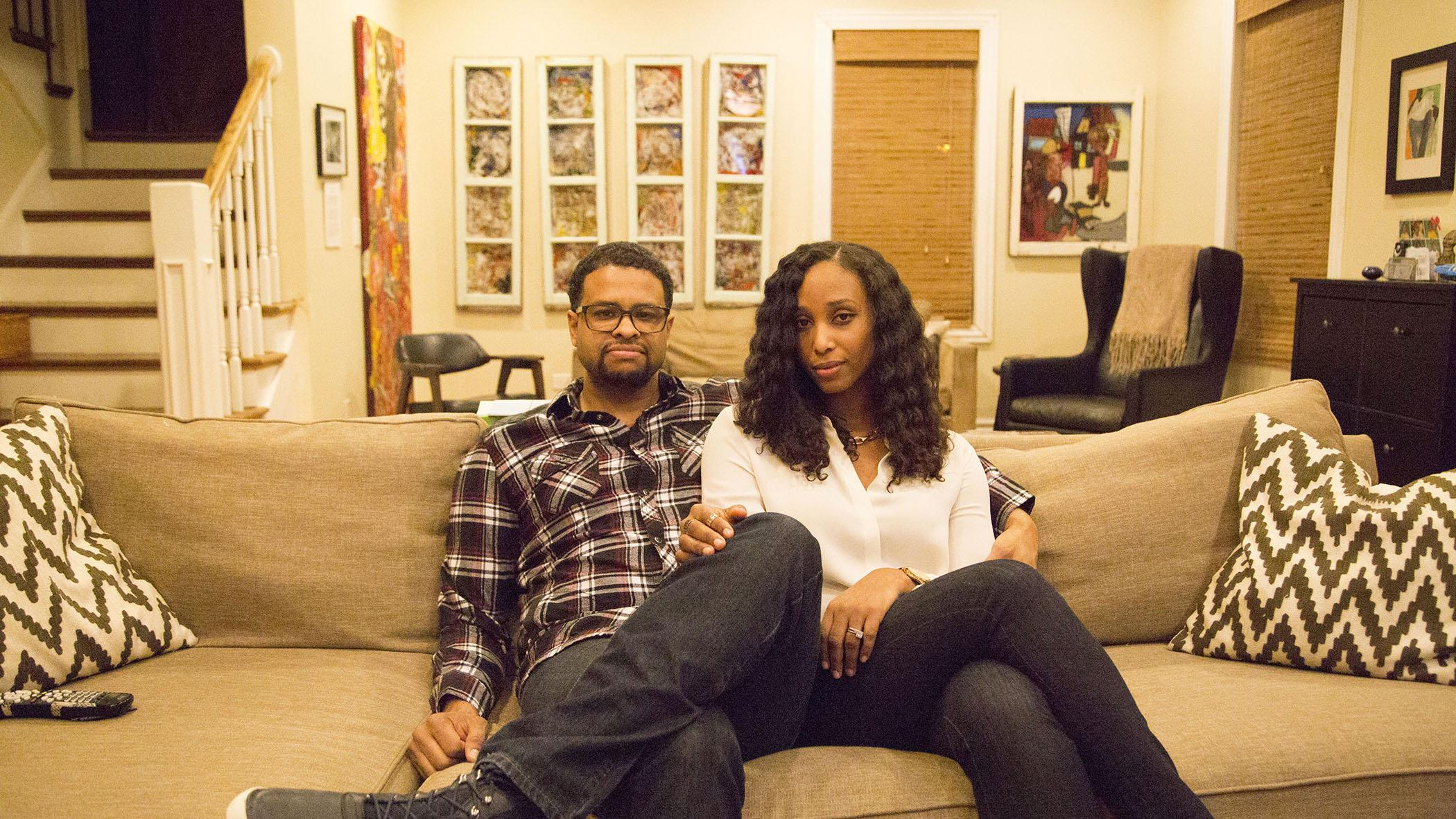 A man and woman sit close to each other on a couch in a homey room decorated with colorful art.