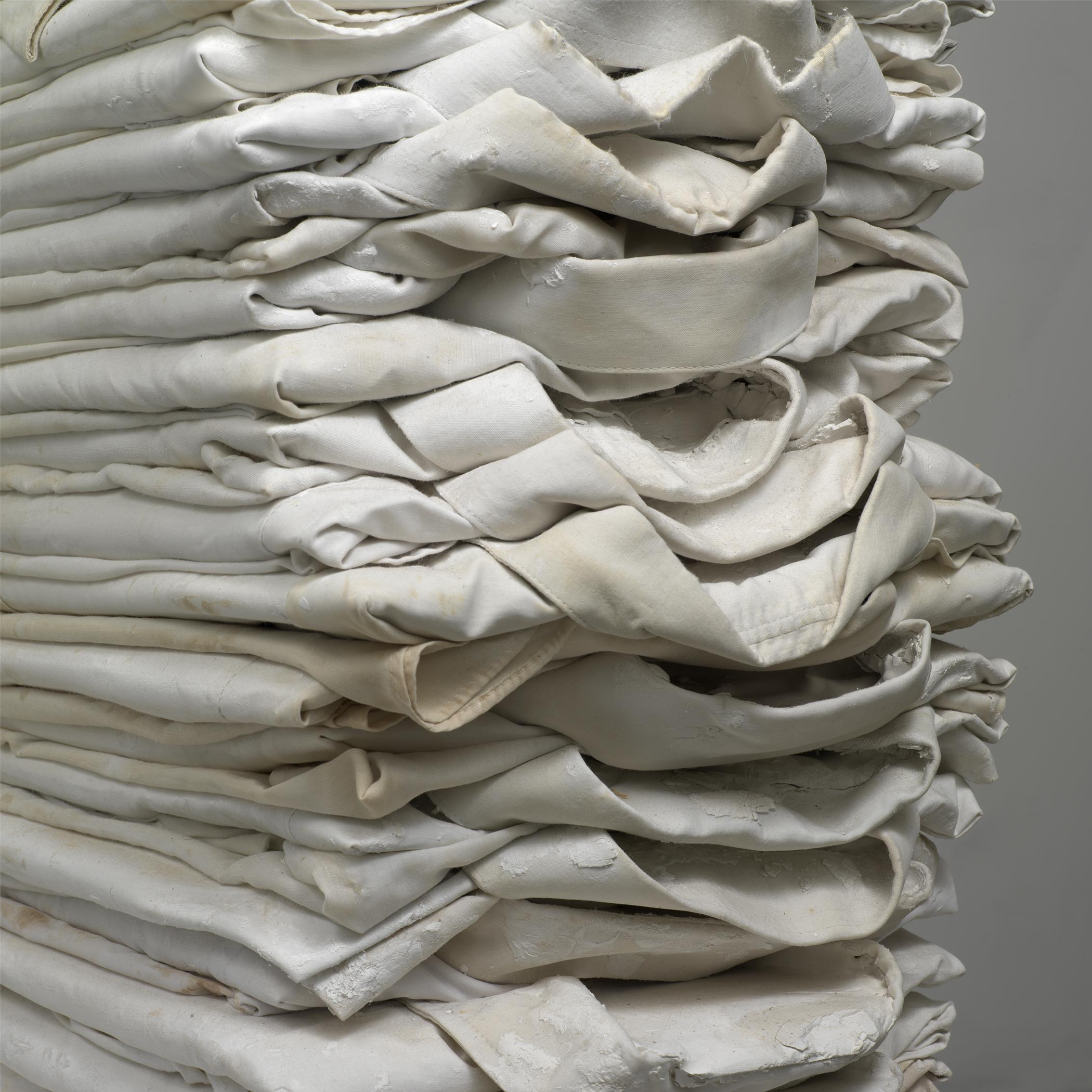 Soiled white dress shirts are folded and stacked on top of one another.