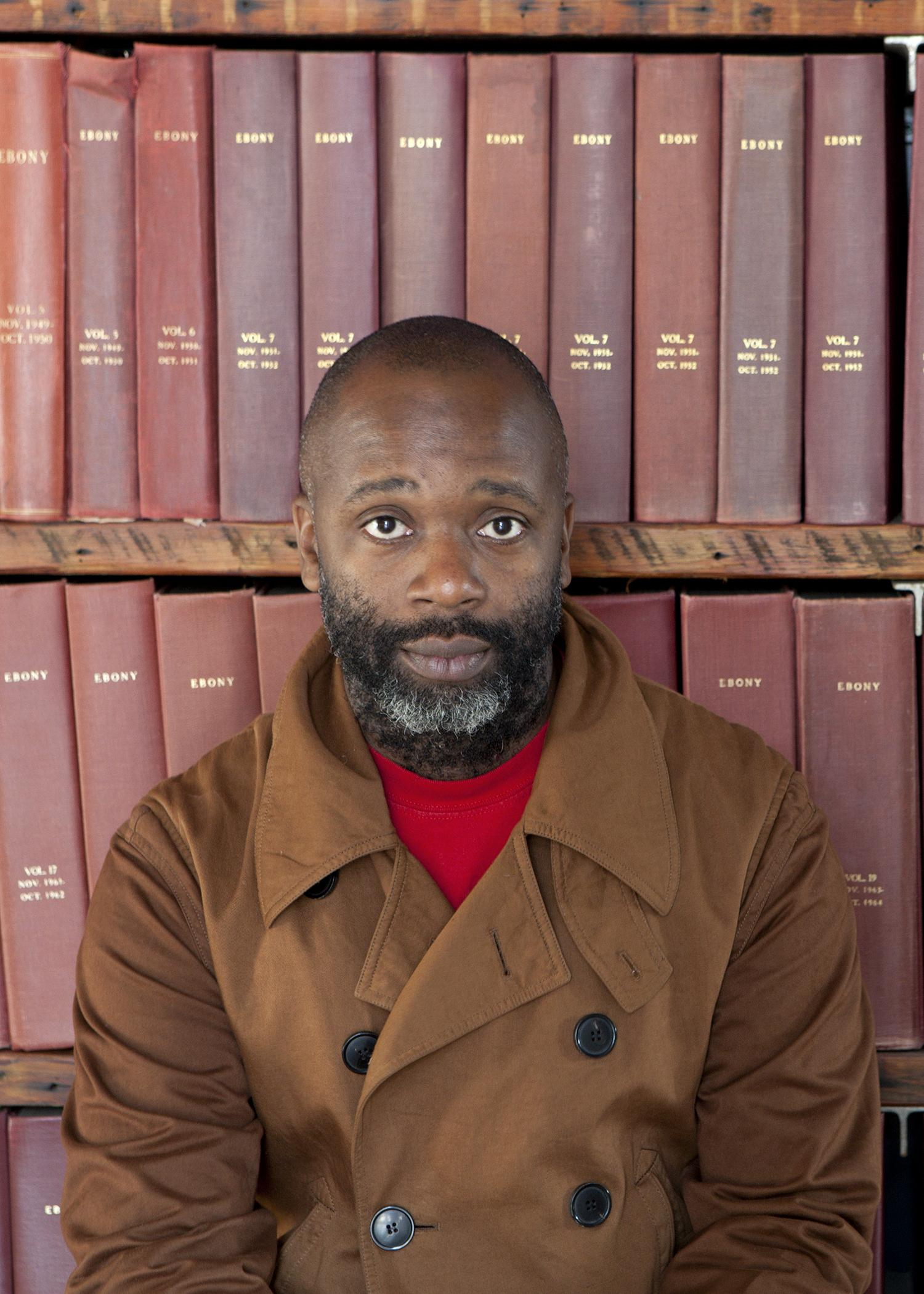 """A dark-skinned person with a beard and wearing a taupe coat sits against shelves of large, reddish-brown books embossed with the word """"EBONY"""" in gold."""