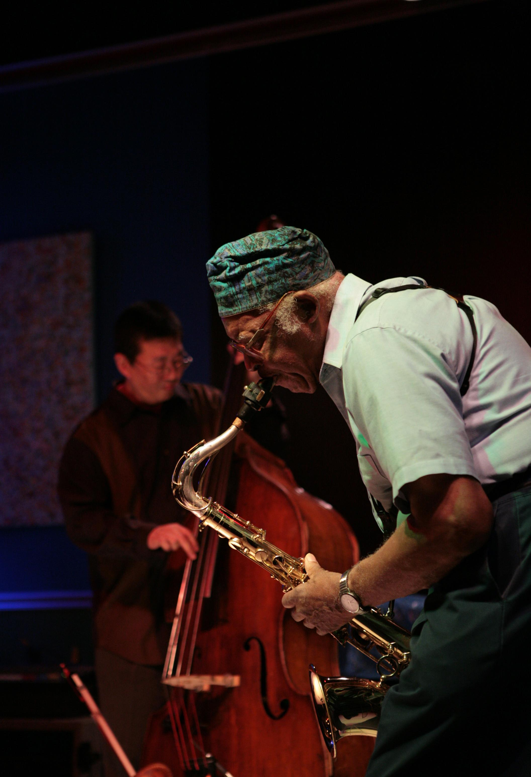 A person wearing a patterned green and blue cap bends forward playing a saxophone, while another person plays standing bass in the background.