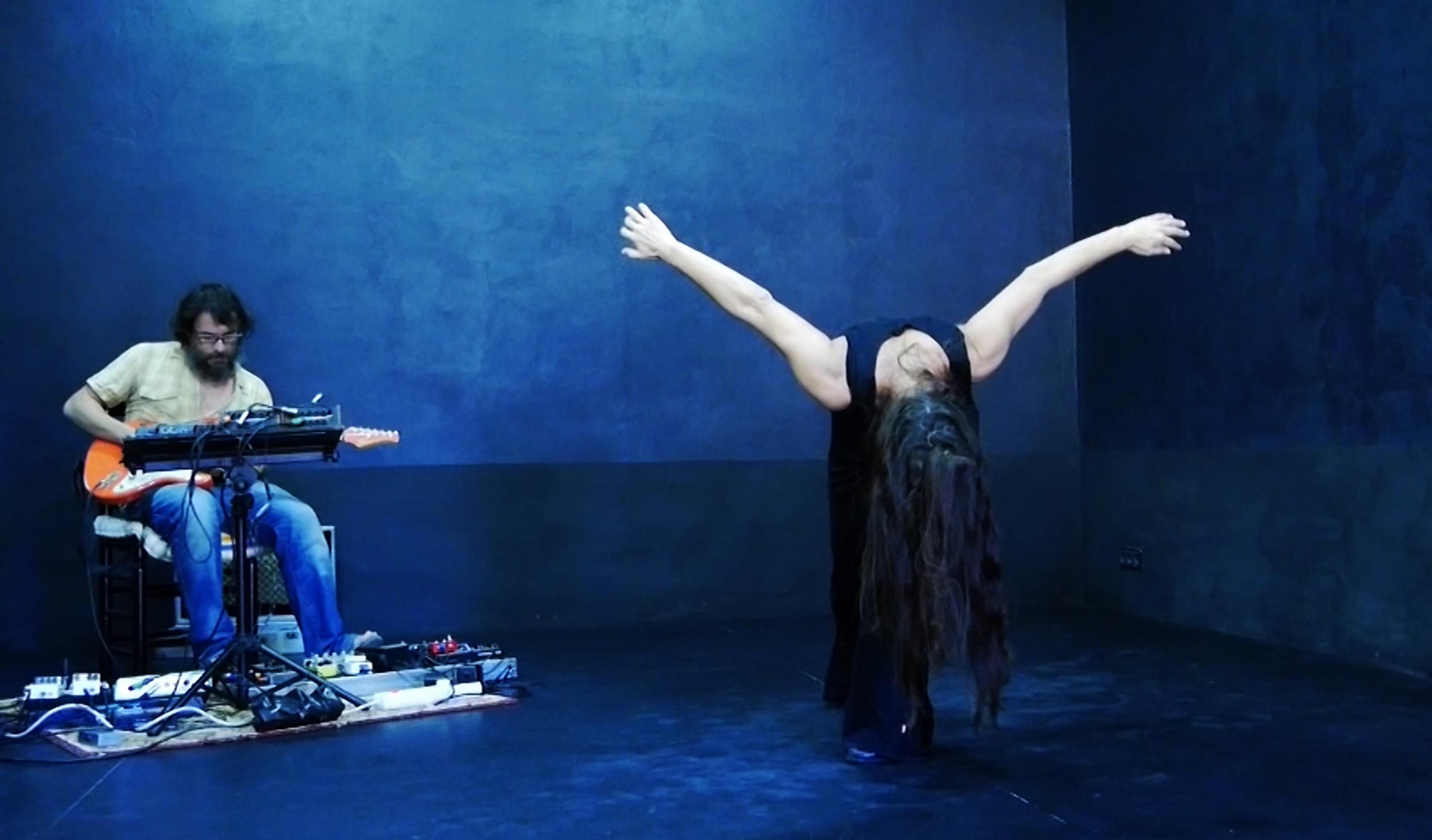 Surrounded by deep blue walls and floor, a person with long hair stands with arms out, bending very far forward while to their right another person plays guitar.
