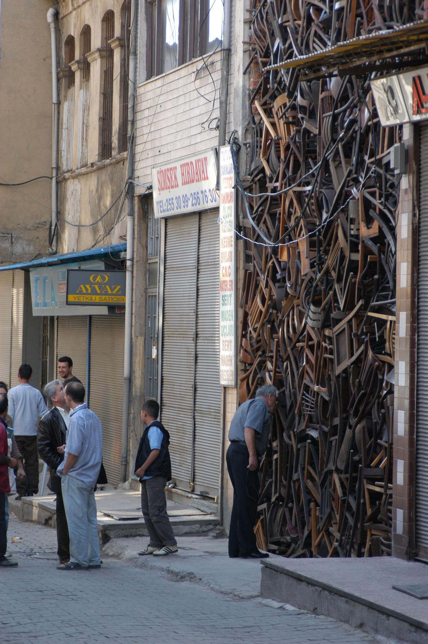 Several passerby on a street marvel at hundreds of chairs placed in a massive pile between two buildings.