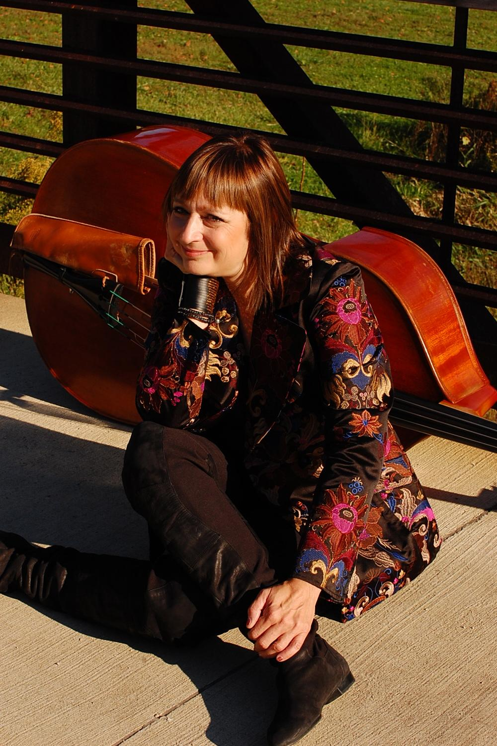 Portrait of a performer sitting with her legs crossed on a sidewalk wearing a floral patterned jacket. A cello is laid on its side behind her; a rustic fence and green grass behind them.