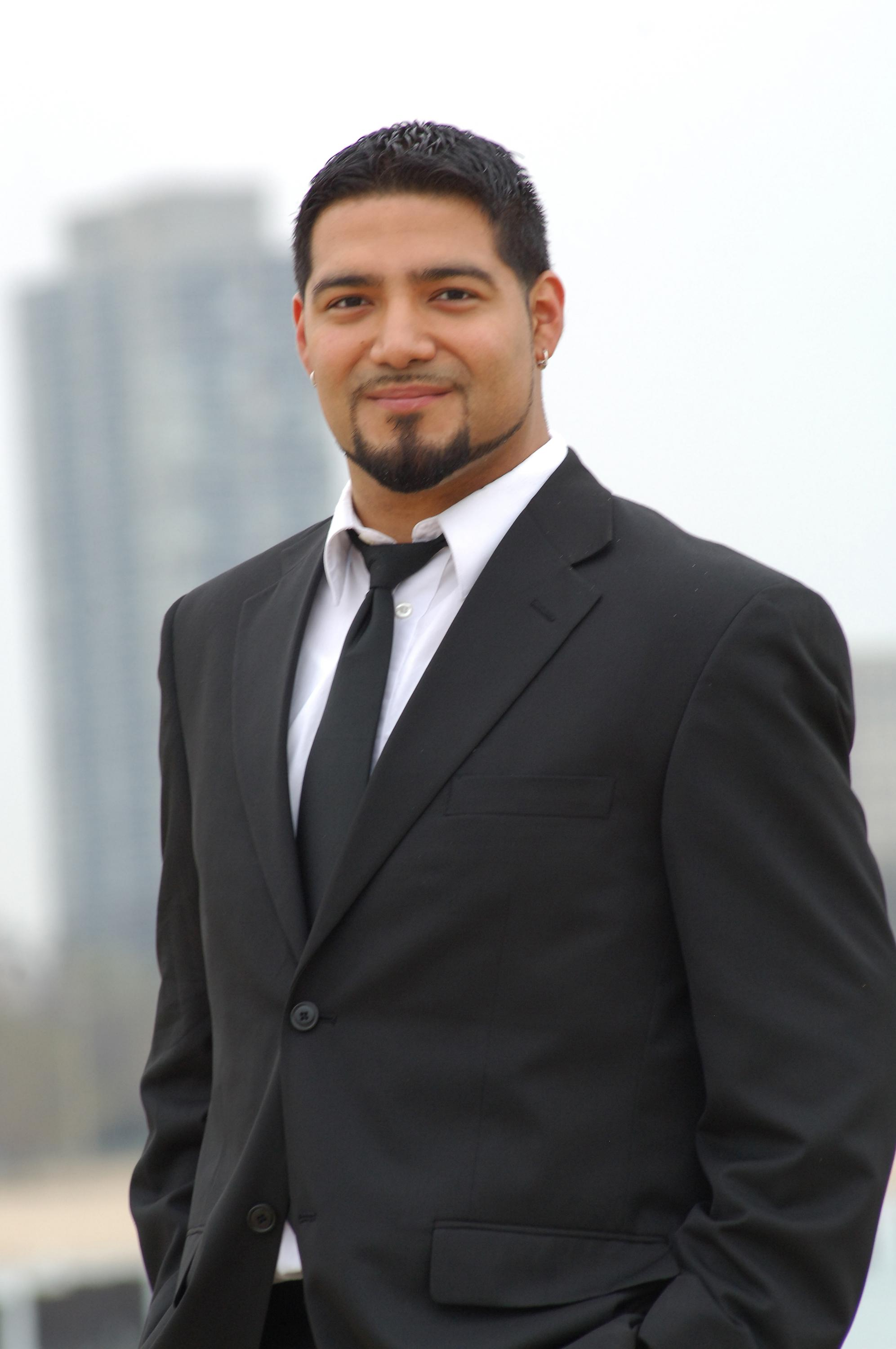 A portrait of a tan-skinned man with short dark hair and a groomed goatee in a black suit and tie, stands outside with skyscrapers blurred in the distance.
