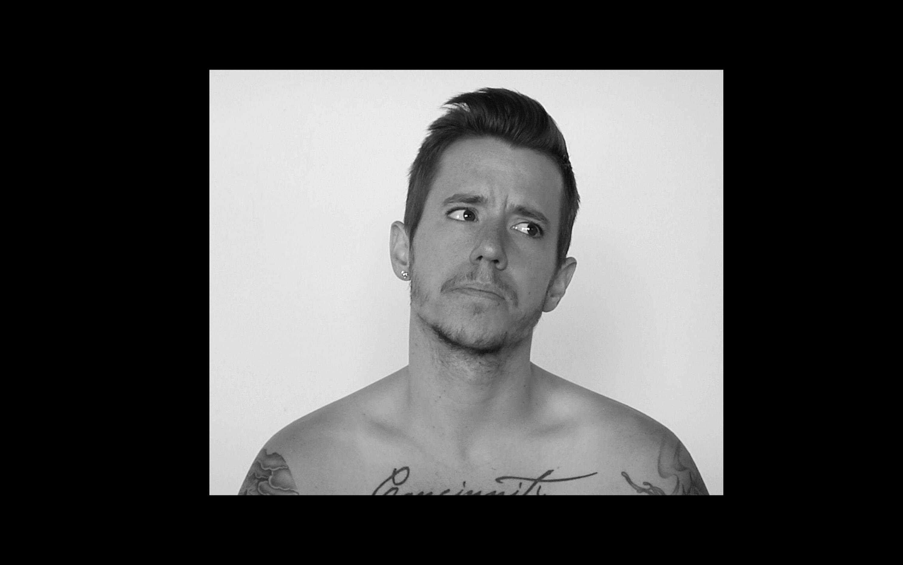 Black and white video still of a young white man's head and torso in front of a white background. He appears shirtless with hair gelled back and looks to his left. He has a mustache and stubble beard, and tattoos on both arms and chest that are cropped by the edge of the frame.